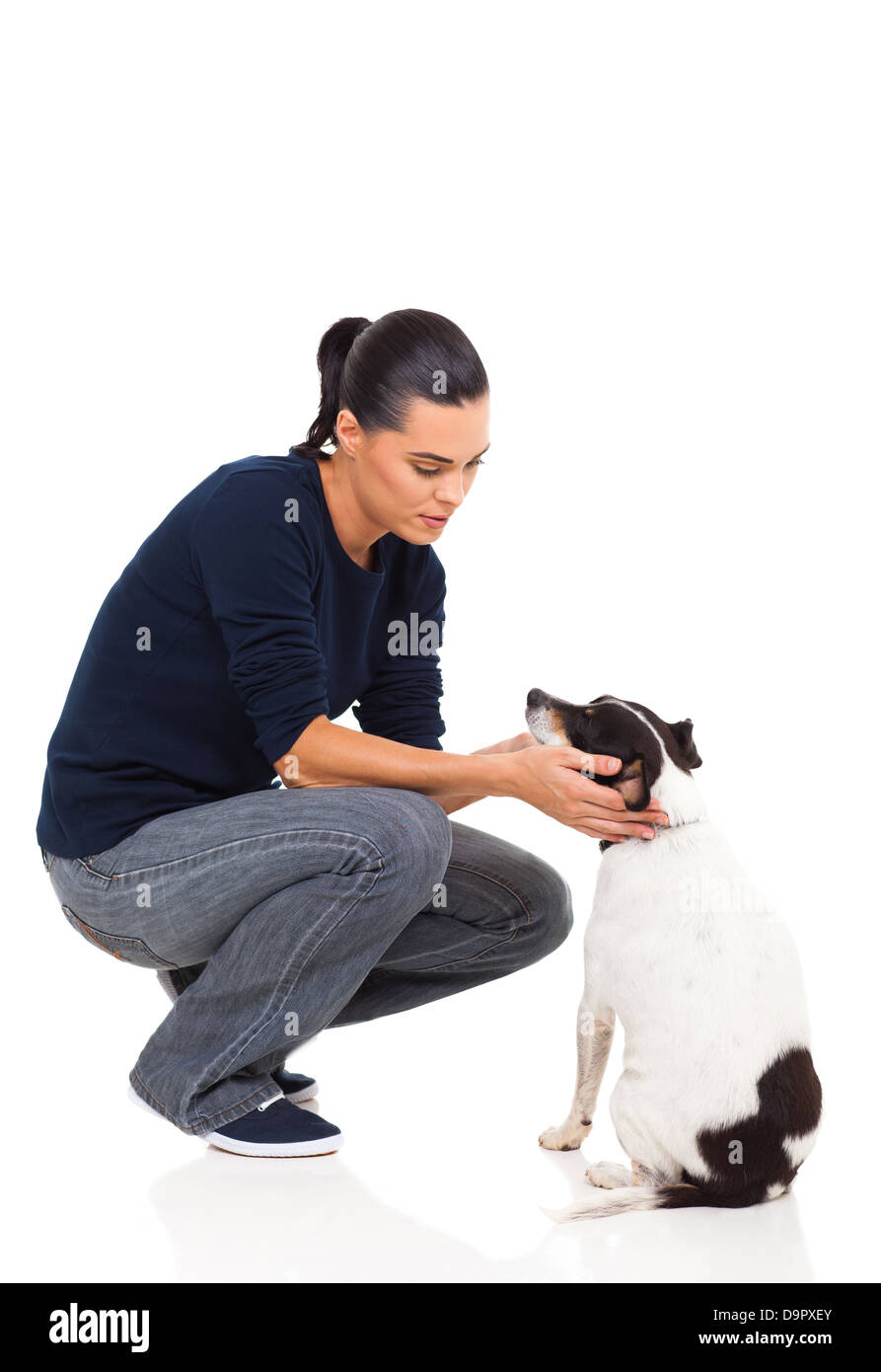 pretty young woman playing with her pet dog on white background - Stock Image