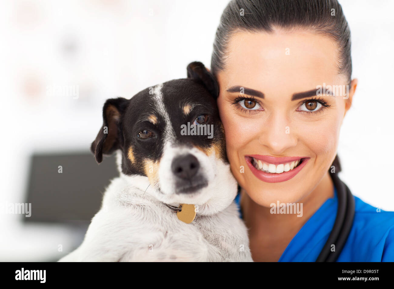 caring female vet holding a dog closeup portrait - Stock Image