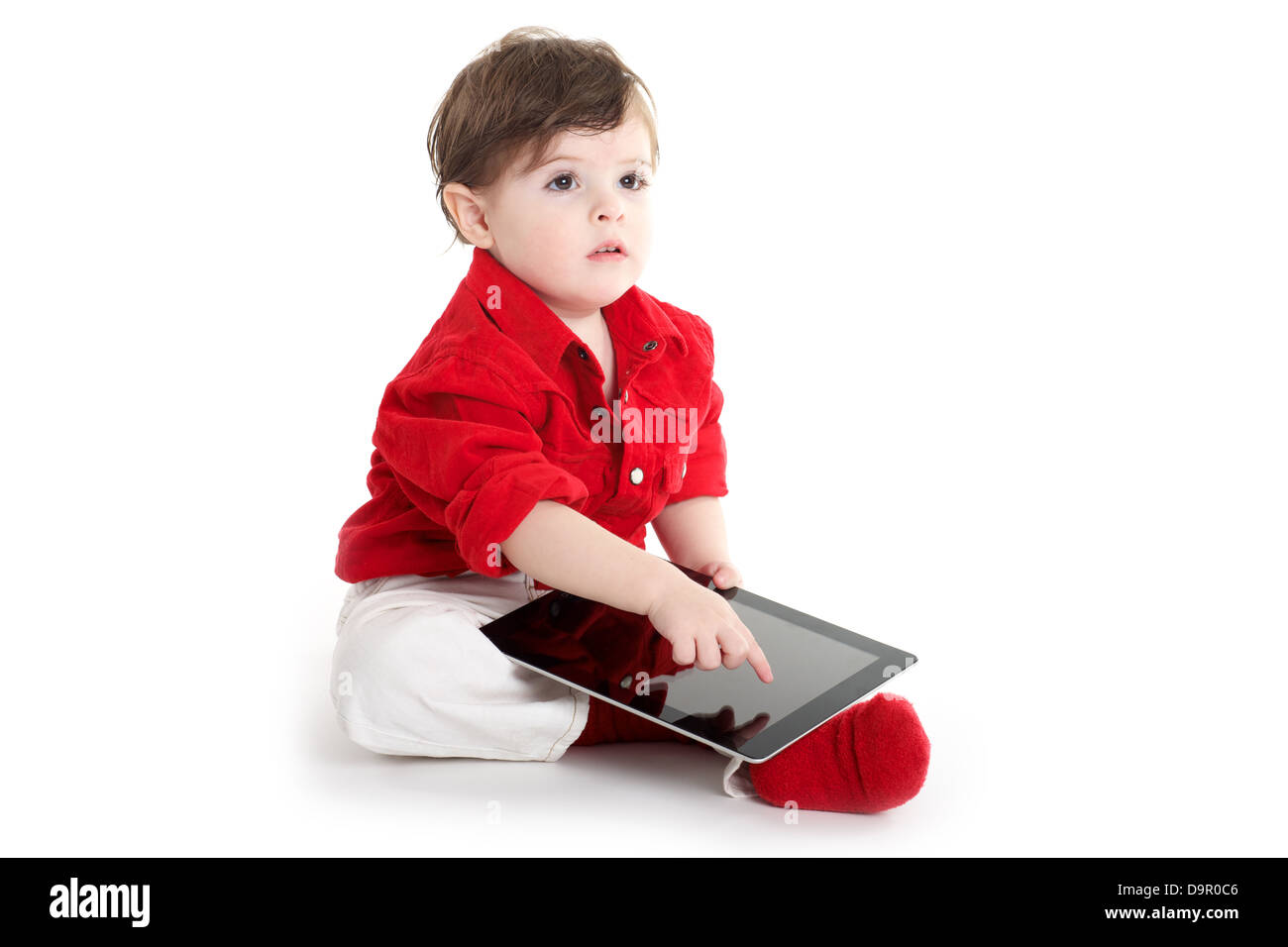 Toddler baby sitting and showing with tablet - Stock Image