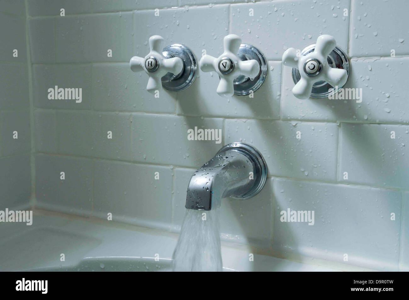 Bathtub fixtures and white subway tile - Stock Image