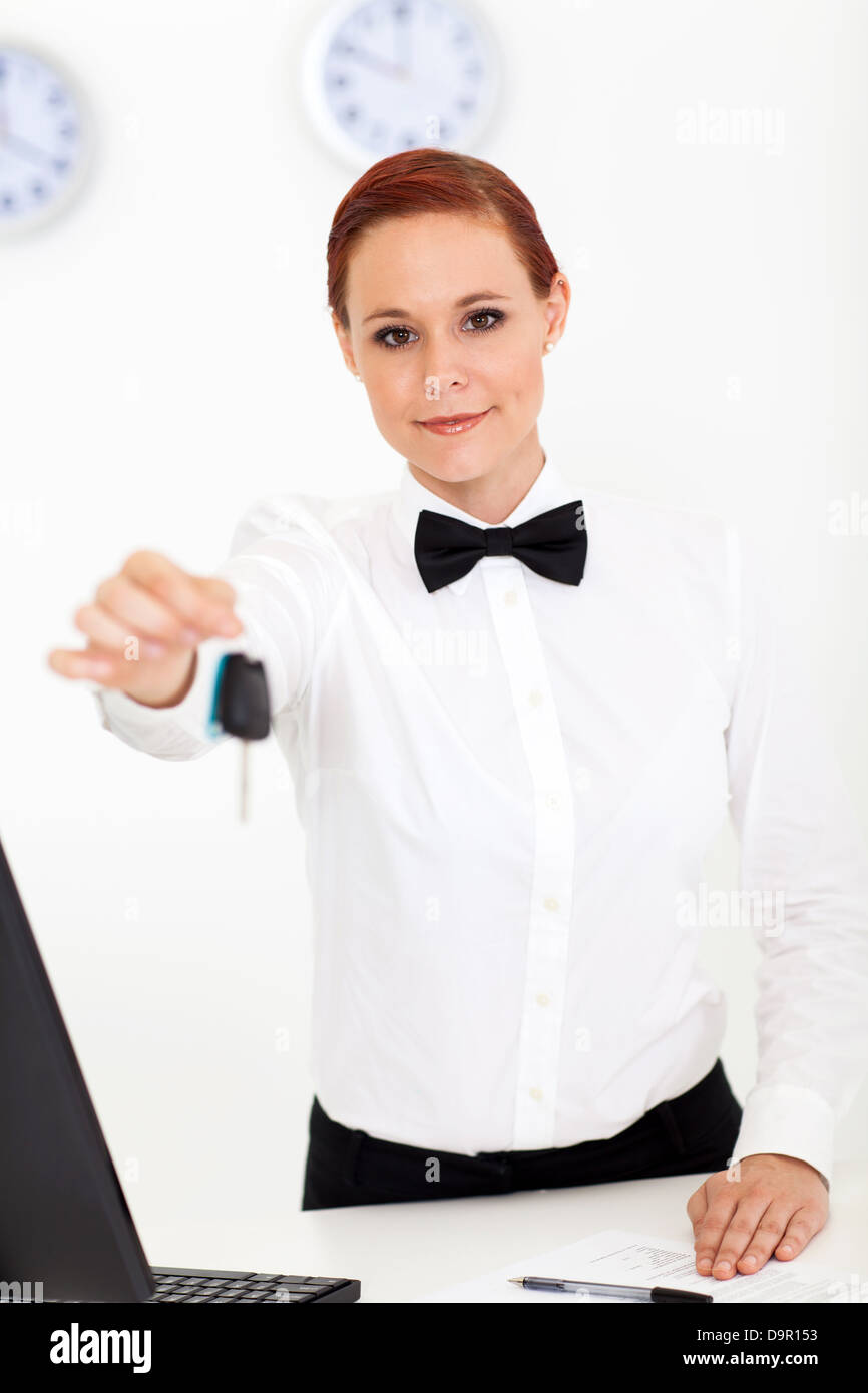young car rental company employee giving key to client Stock Photo