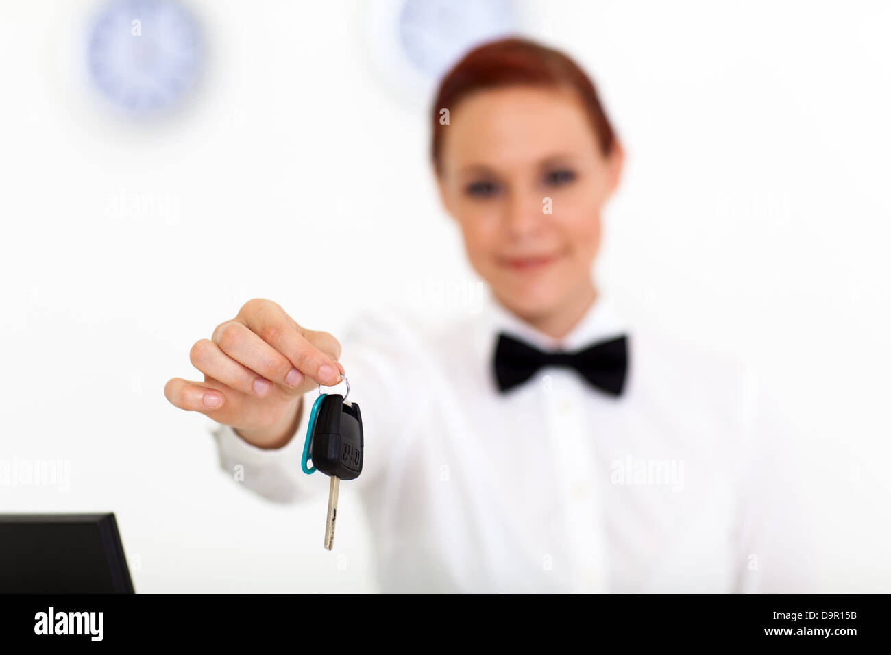 car rental company employee hand over car key to client - Stock Image