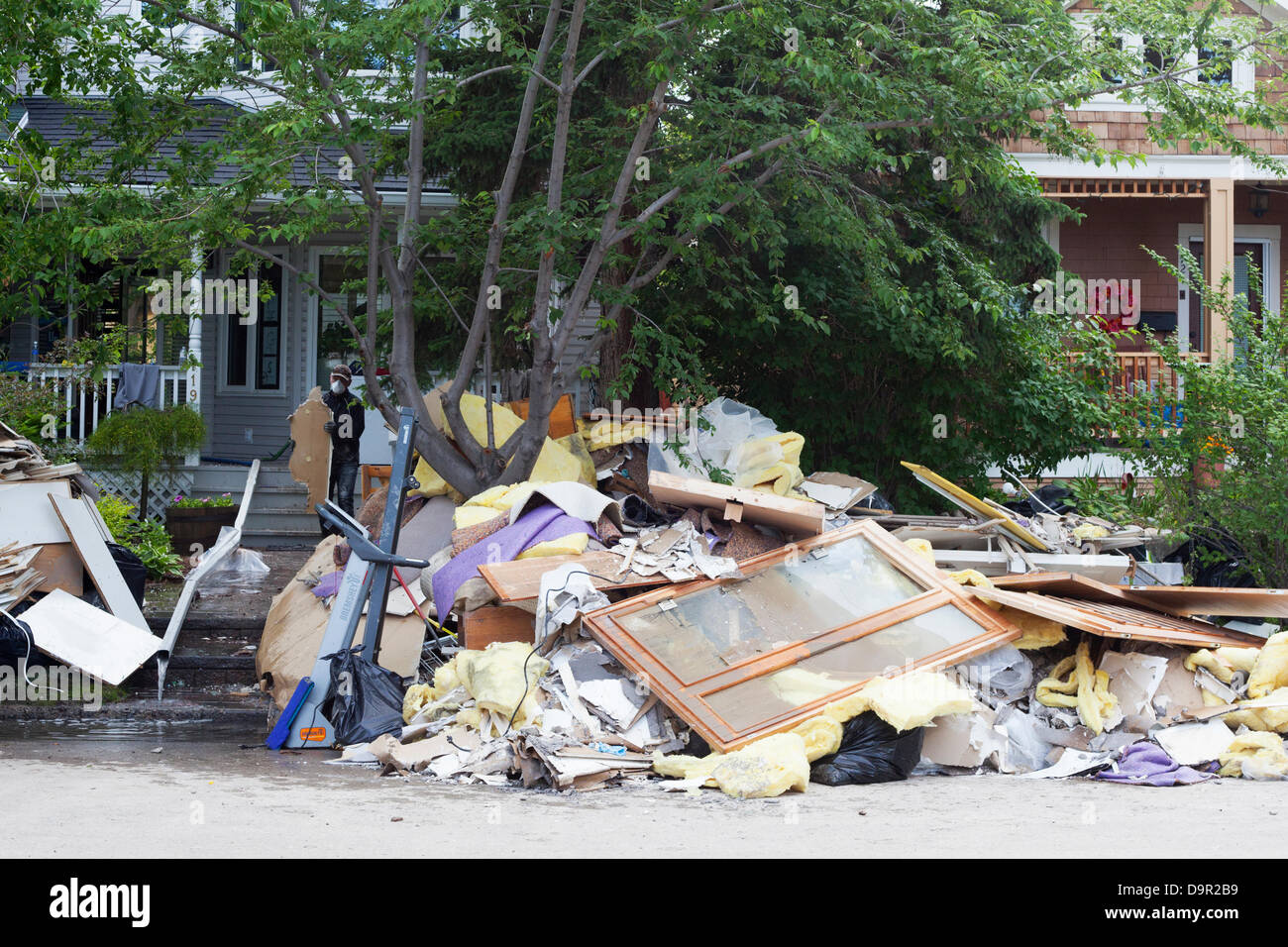 Man removes items from a house as cleanup begins after floodwaters recede from the Sunnyside neighbourhood of Calgary, - Stock Image