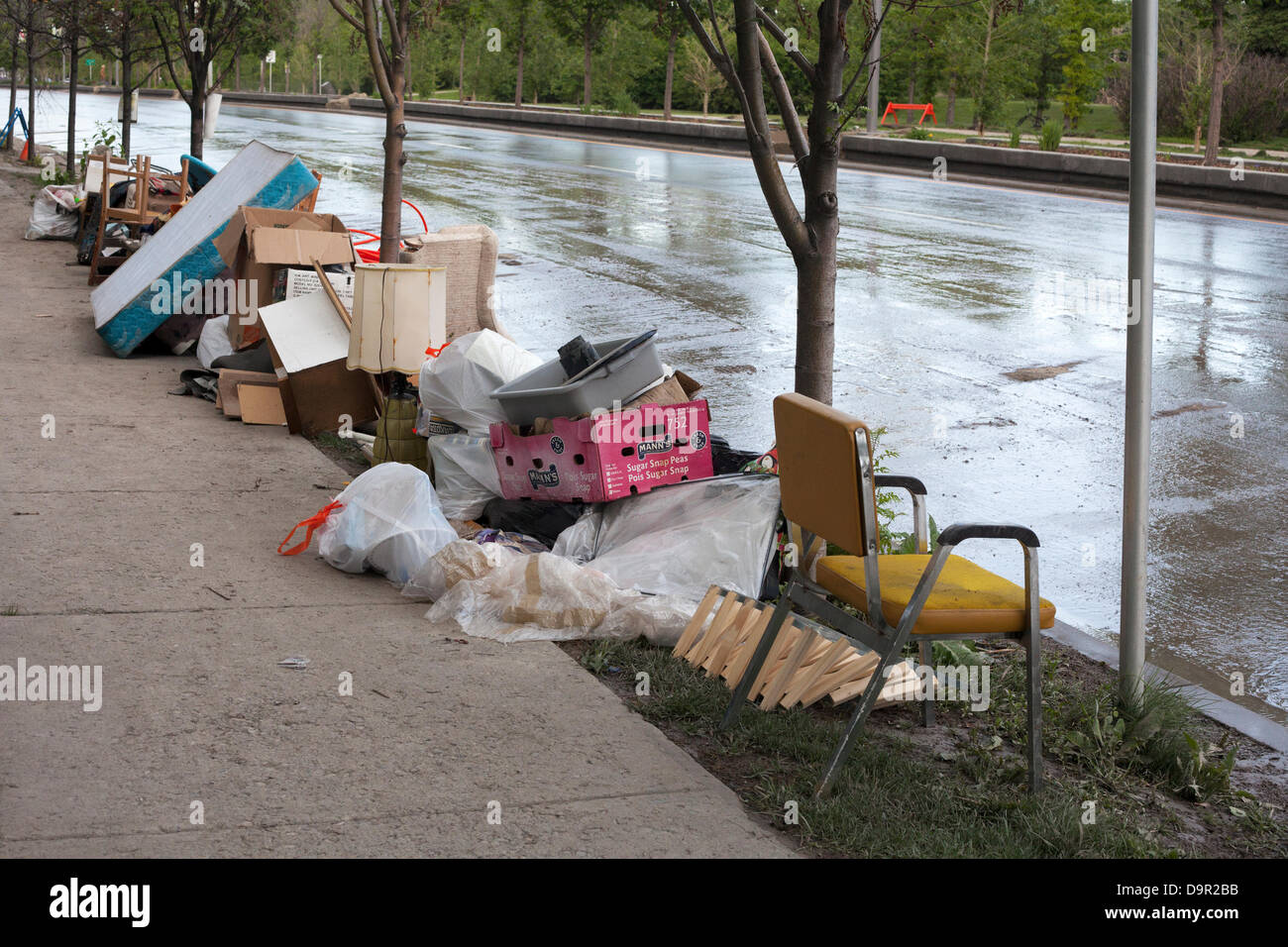 Waterlogged household items pile up along Memorial Drive as cleanup begins after floodwaters recede from the Sunnyside Stock Photo