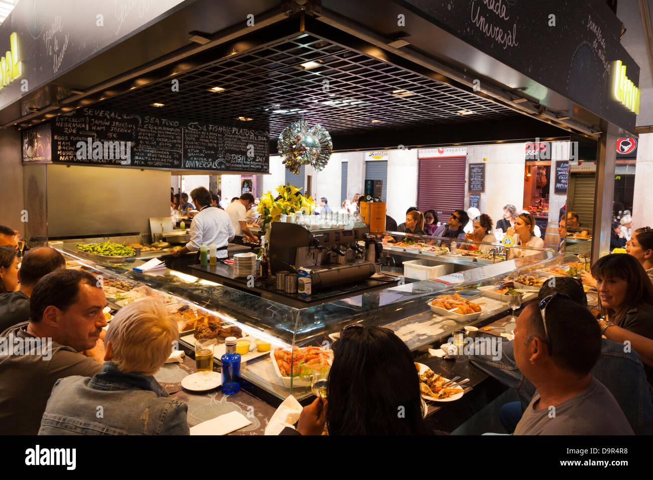customers seated around a fish fast food cafe in La Boqueria Market Barcelona - Stock Image