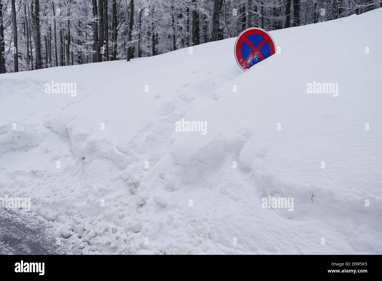 A road sign almost covered in a snowdrift, - Stock Image