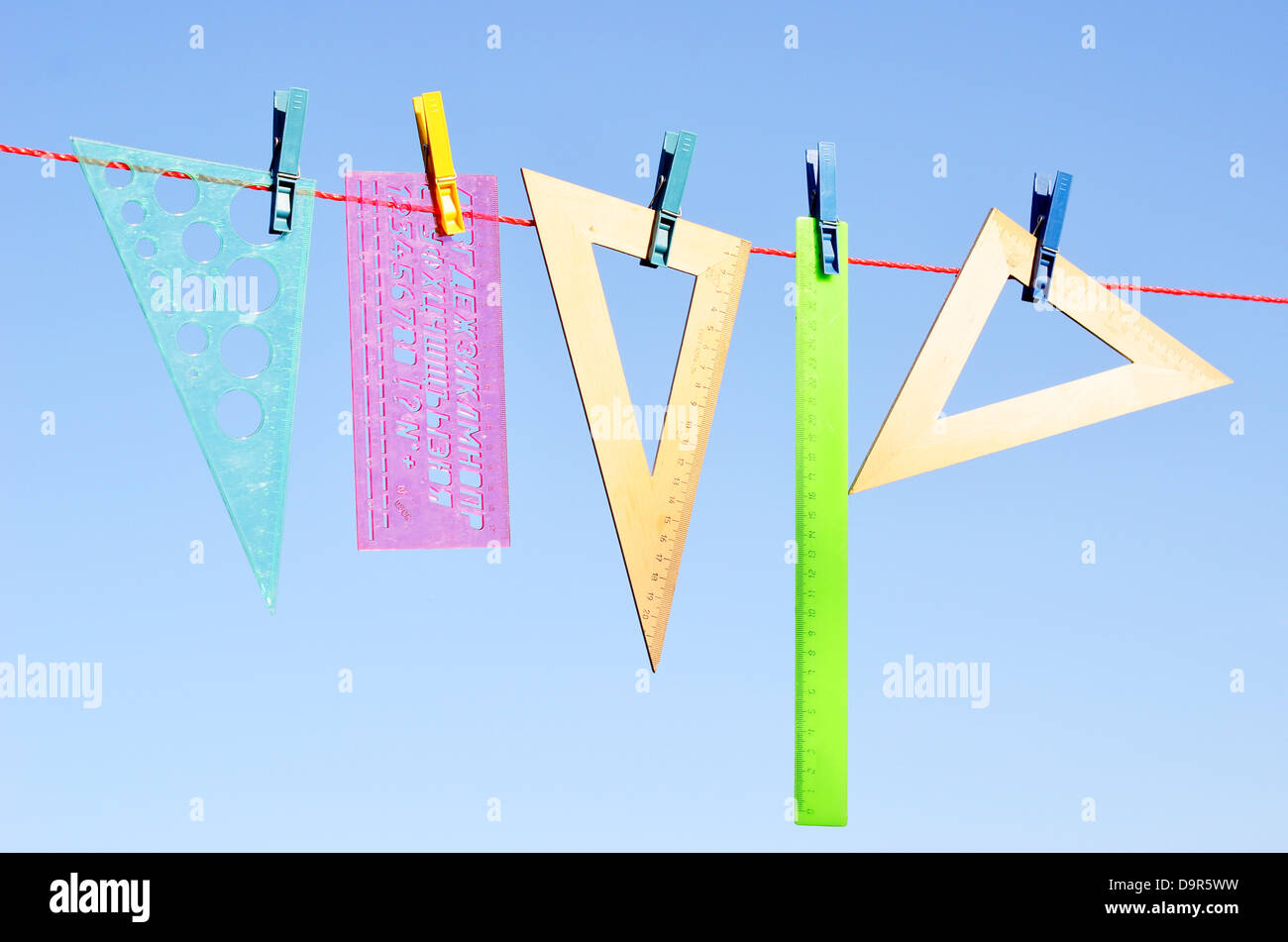 wooden and plastic rulers on washing line against sky - Stock Image