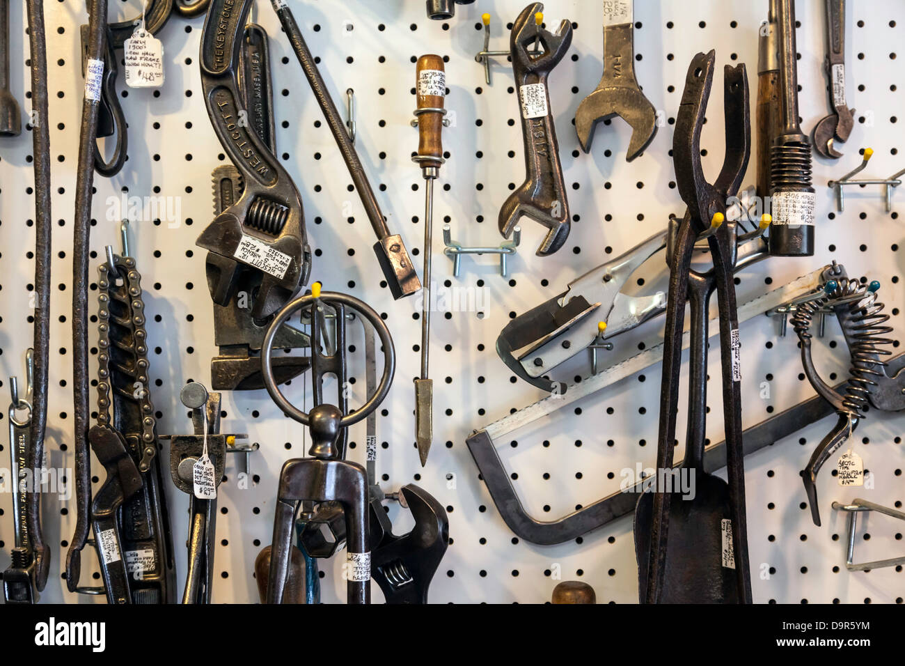 Assorted vintage tools and accessories hanging on a white pegboard. - Stock Image