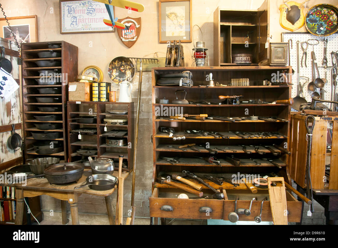 Vintage cast iron pots, pans and tools stored on tables and in drawers and wooden racks.  Pictures and tools hang - Stock Image