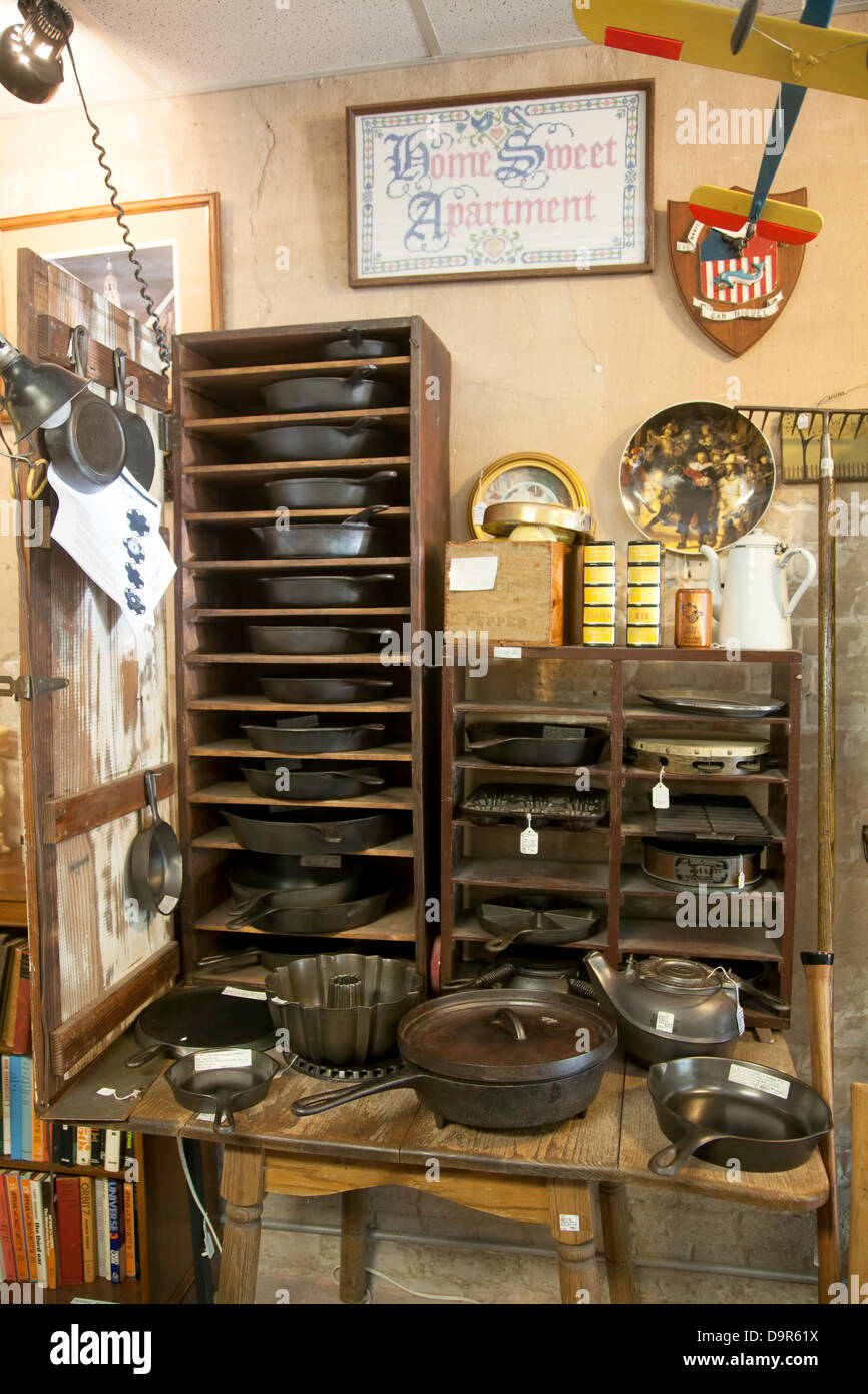 Assorted vintage cast iron pots and pans stored in a wooden rack and setting on a wood table.  A needlepoint hangs - Stock Image