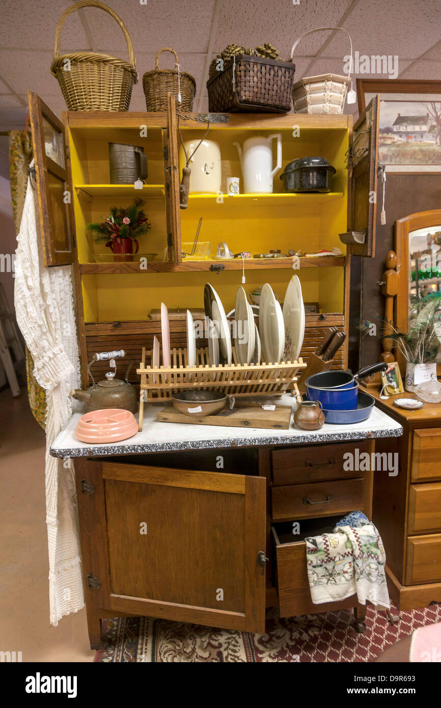 Vintage dishes, pots, pans baskets and accessories displayed on a compact free-standing kitchen cabinet. - Stock Image