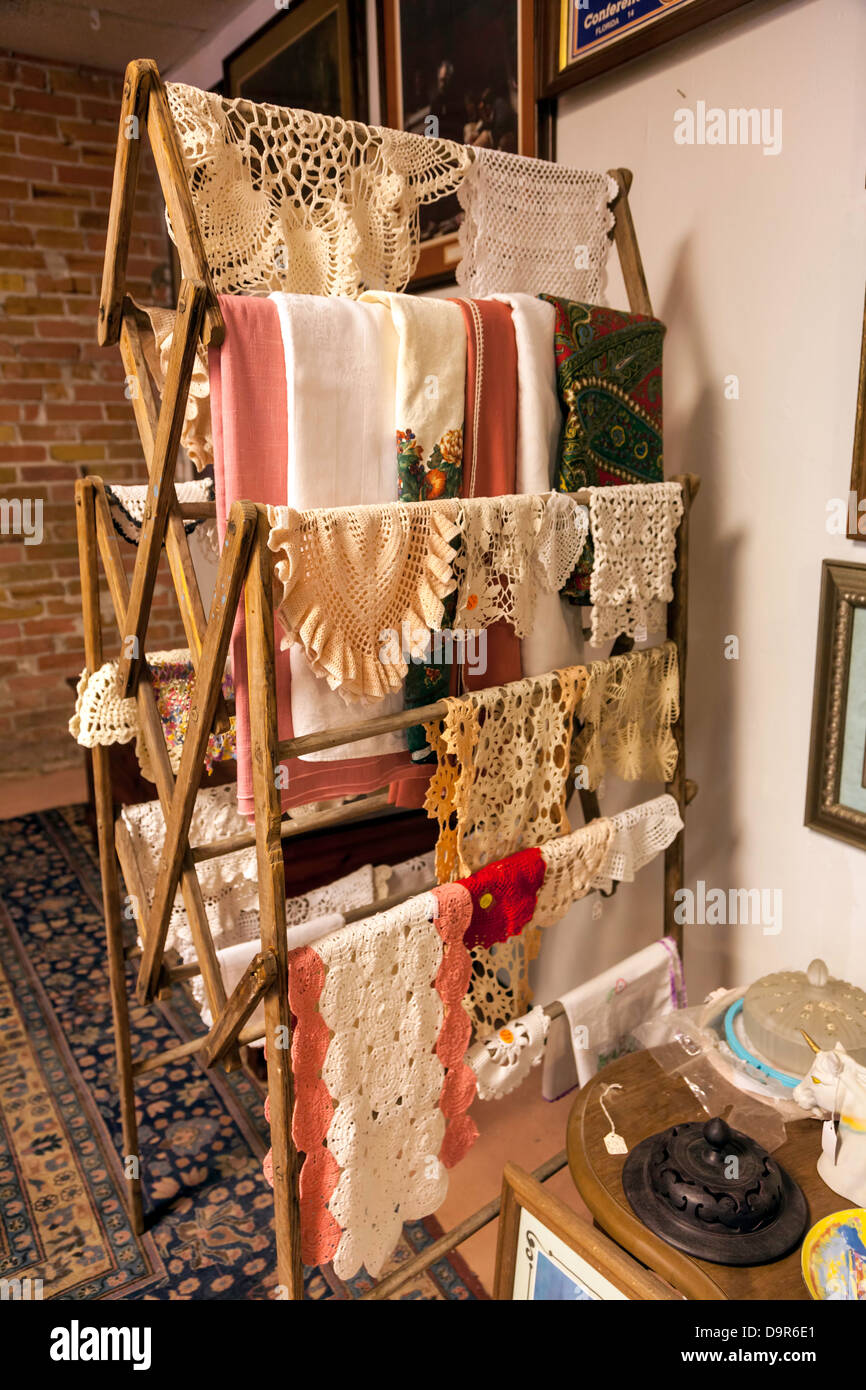 Vintage linens and crocheted doilies and tablecloths on a drying rack. - Stock Image