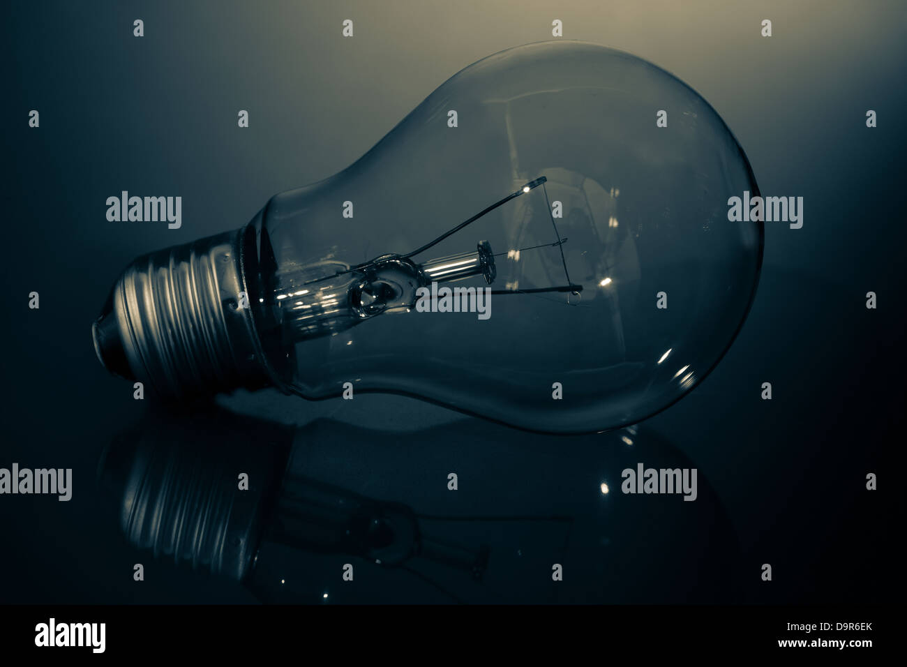 Clear light bulb lay on its side in darkness Stock Photo