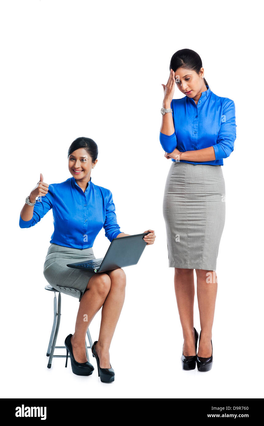 Businesswoman celebrating her success with her clone standing beside her - Stock Image