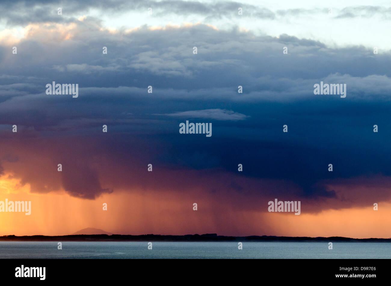 Great dark gray stormy cloud puring rain above the ocean. - Stock Image