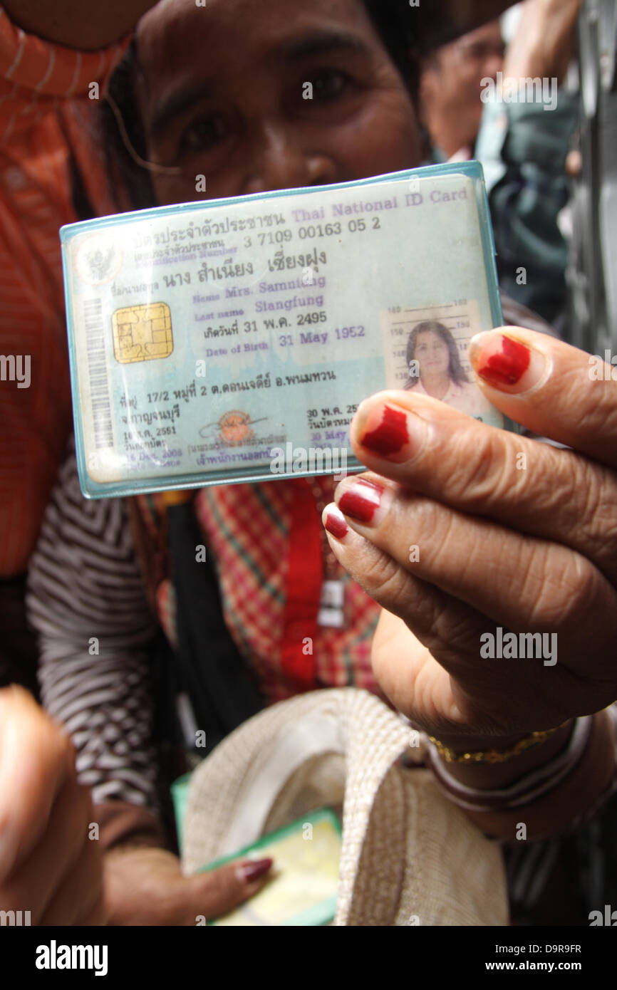 Bangkok , Thailand . 25th June 2013 . Thai farmers wait outside the Government showing their ID cards. Thai farmers - Stock Image