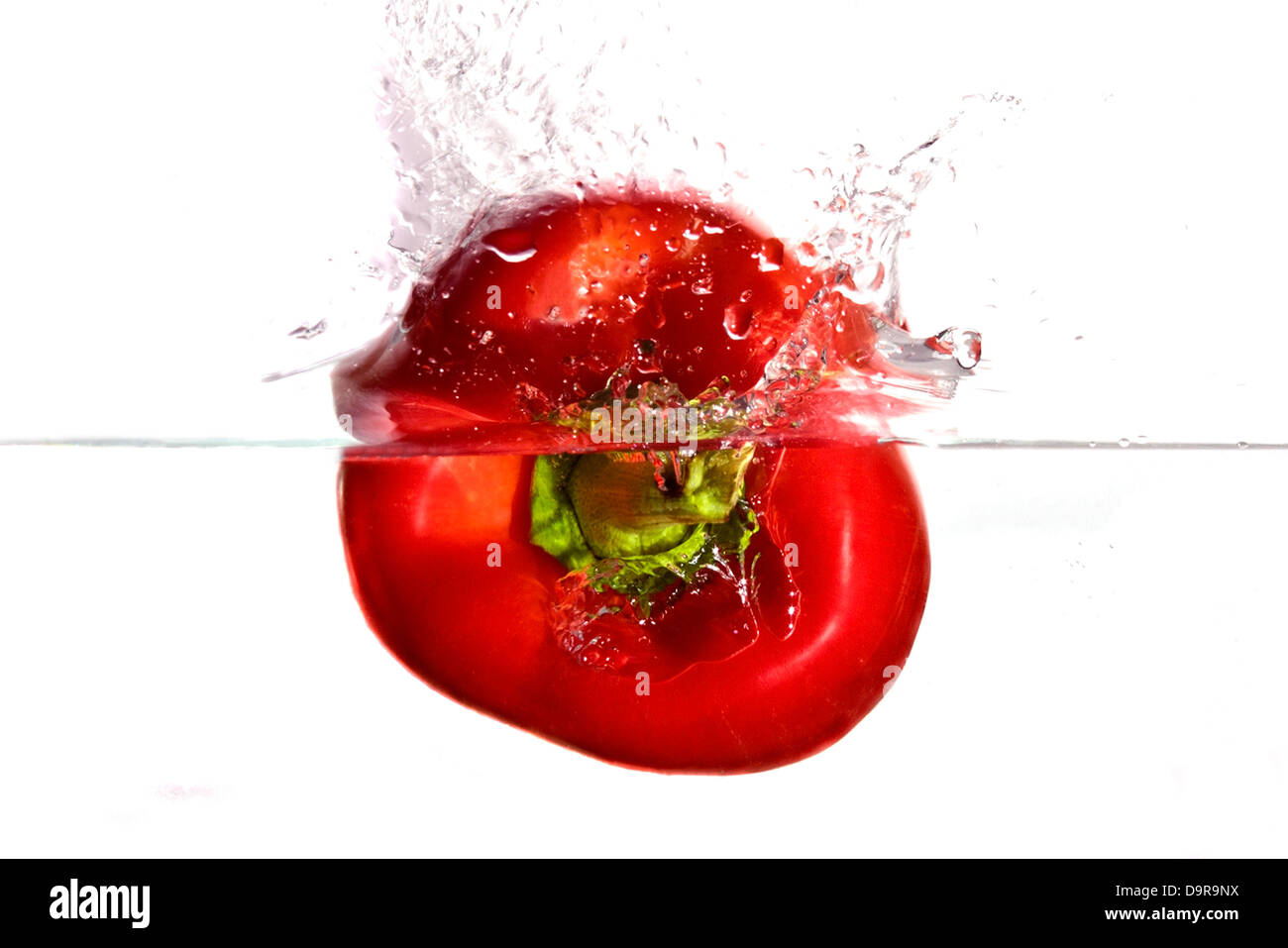 Red pepper plunging in water - Stock Image