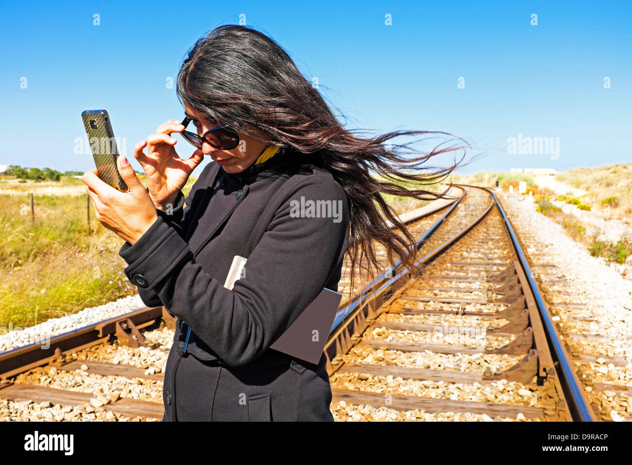 Young beautiful woman reading an sms on a railroad track - Stock Image