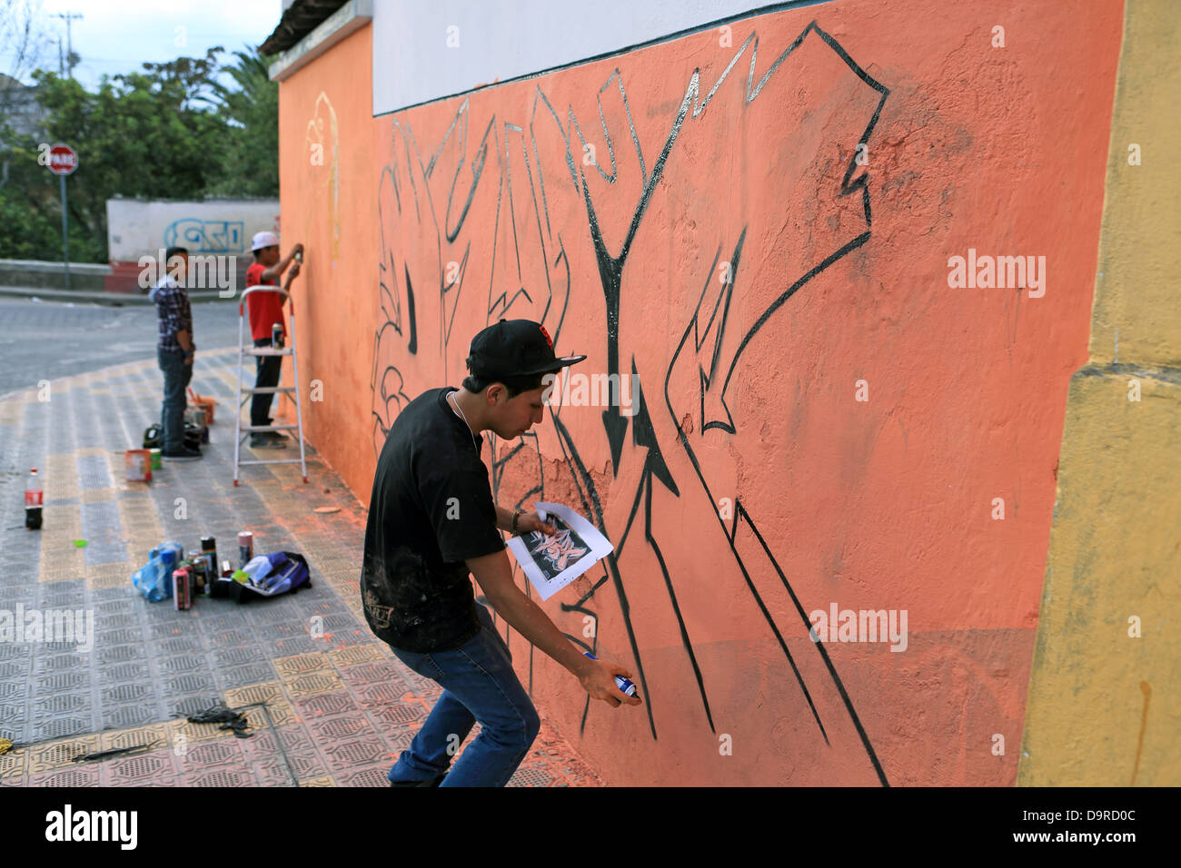 Teenage street artists creating graffiti with local authority permission in the streets of Otavalo, Ecuador - Stock Image