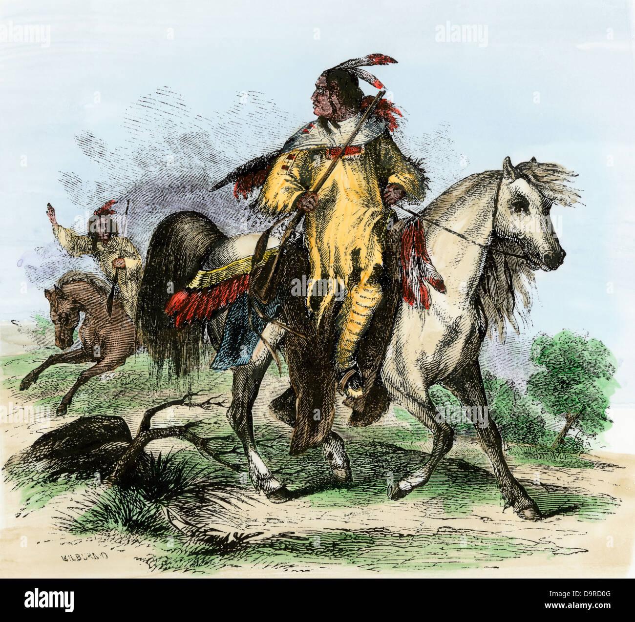 Blackfeet warriors carrying guns on horseback, 1850s. Hand-colored woodcut - Stock Image