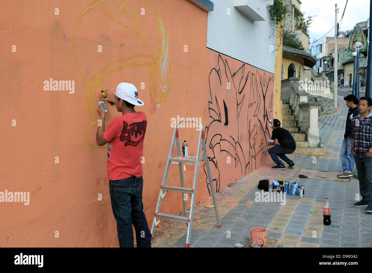 Teenage Street Artists Creating Graffiti With Local Authority Permission In The Streets Of Otavalo Ecuador