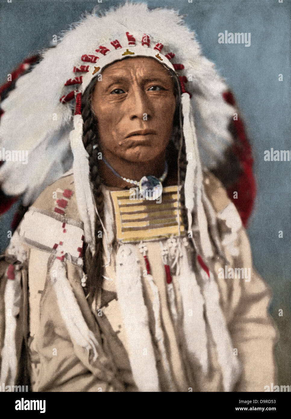 Crow Indian chief in a traditional war bonnet and clothing, circa 1900. Hand-colored halftone of a photograph - Stock Image