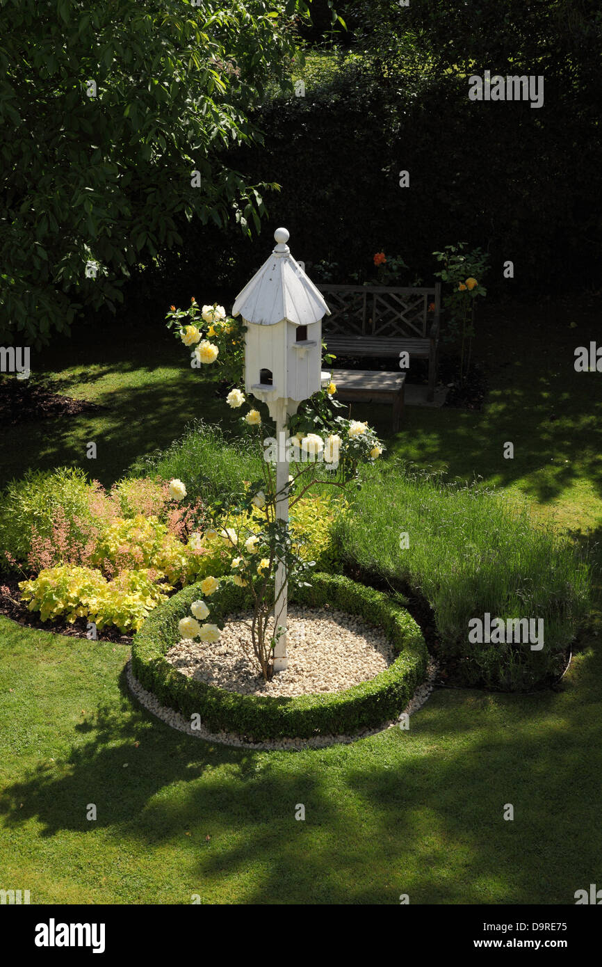 A white dovecote encircled by low box hedging and white stones with a yellow rose growing up it in a garden setting - Stock Image