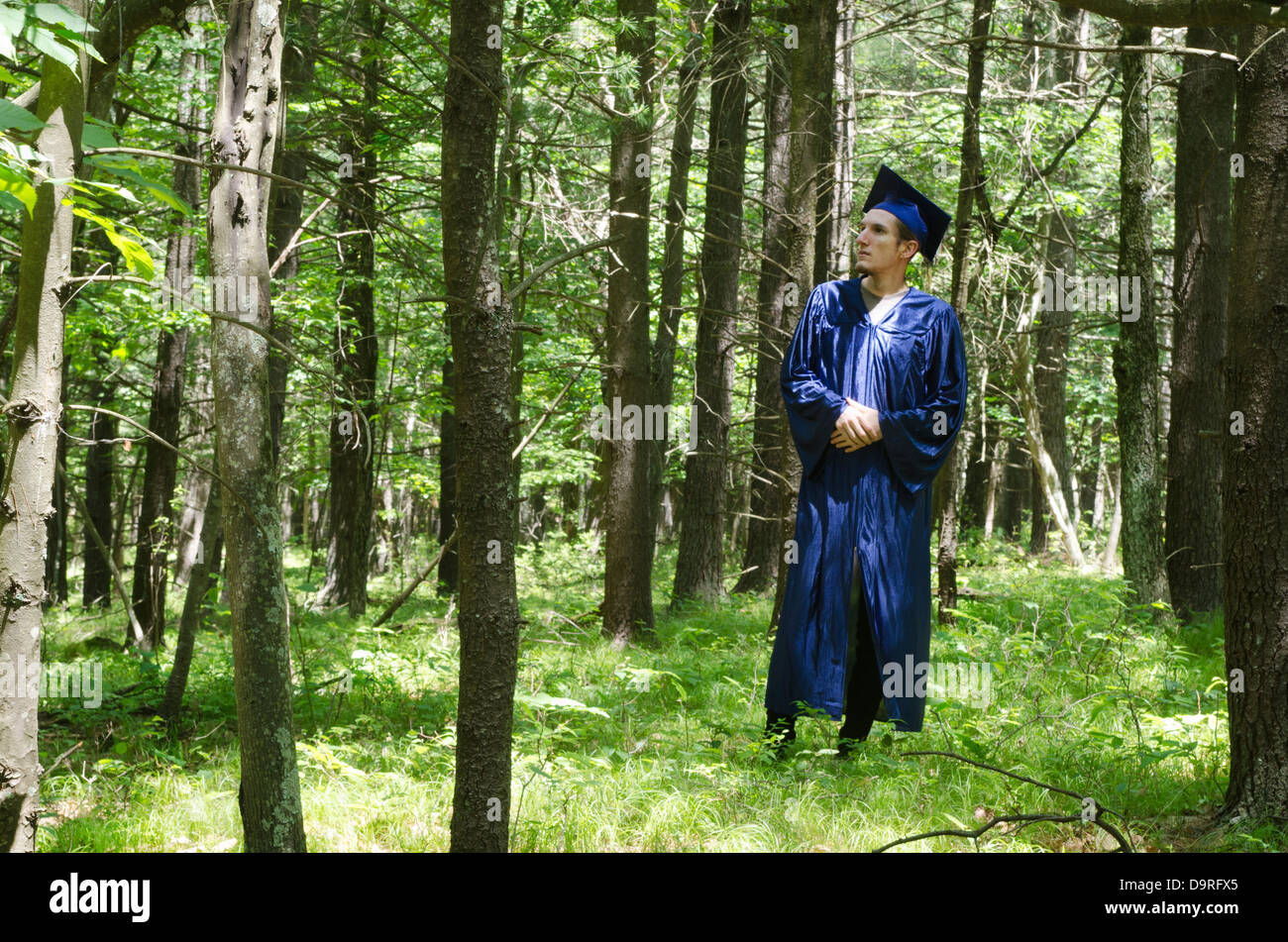 graduate student standing in forest - Stock Image
