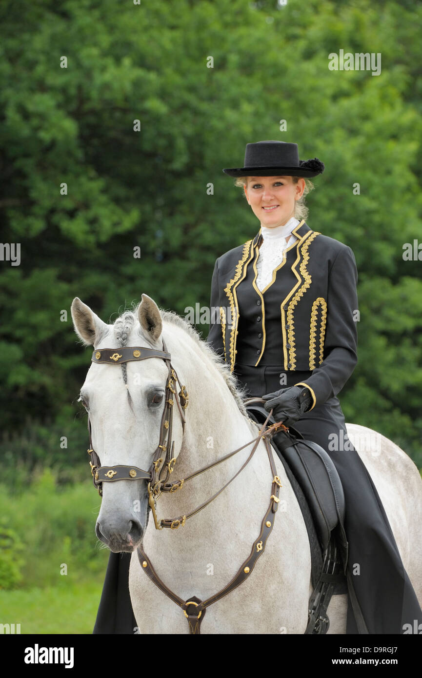 Woman on back of her Lusitano horse stallion wearing a portuguese outfit - Stock Image