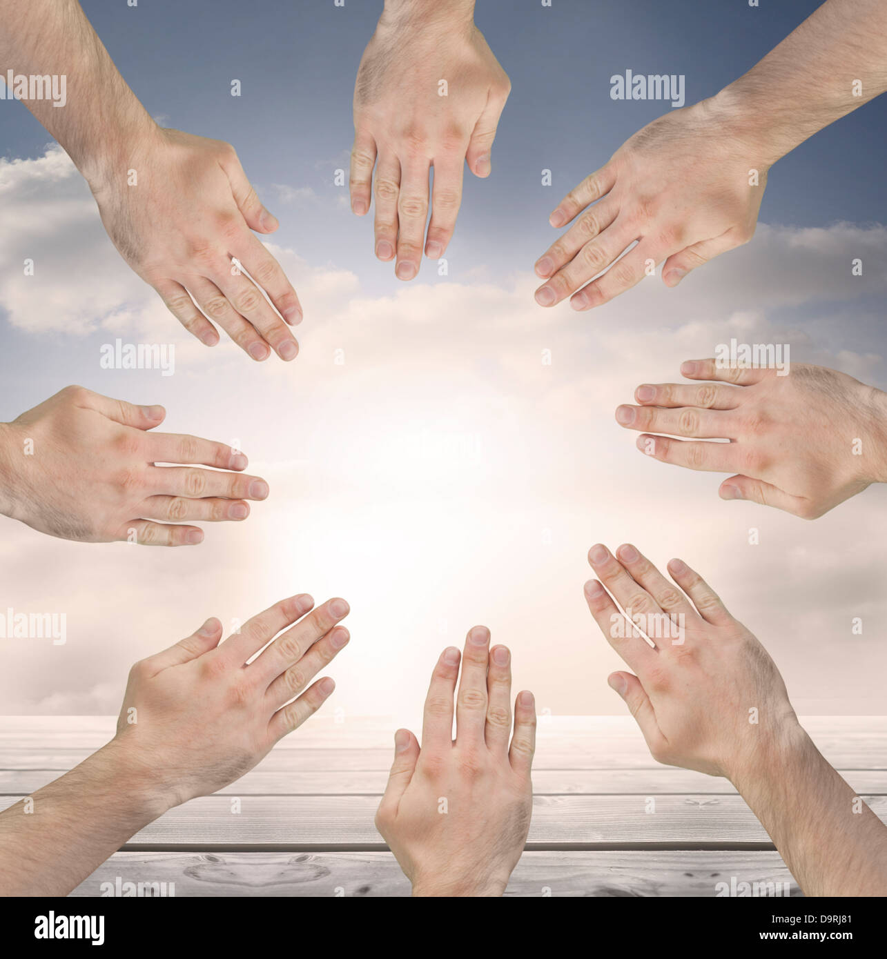Group of hands forming a circle over blue sky - Stock Image