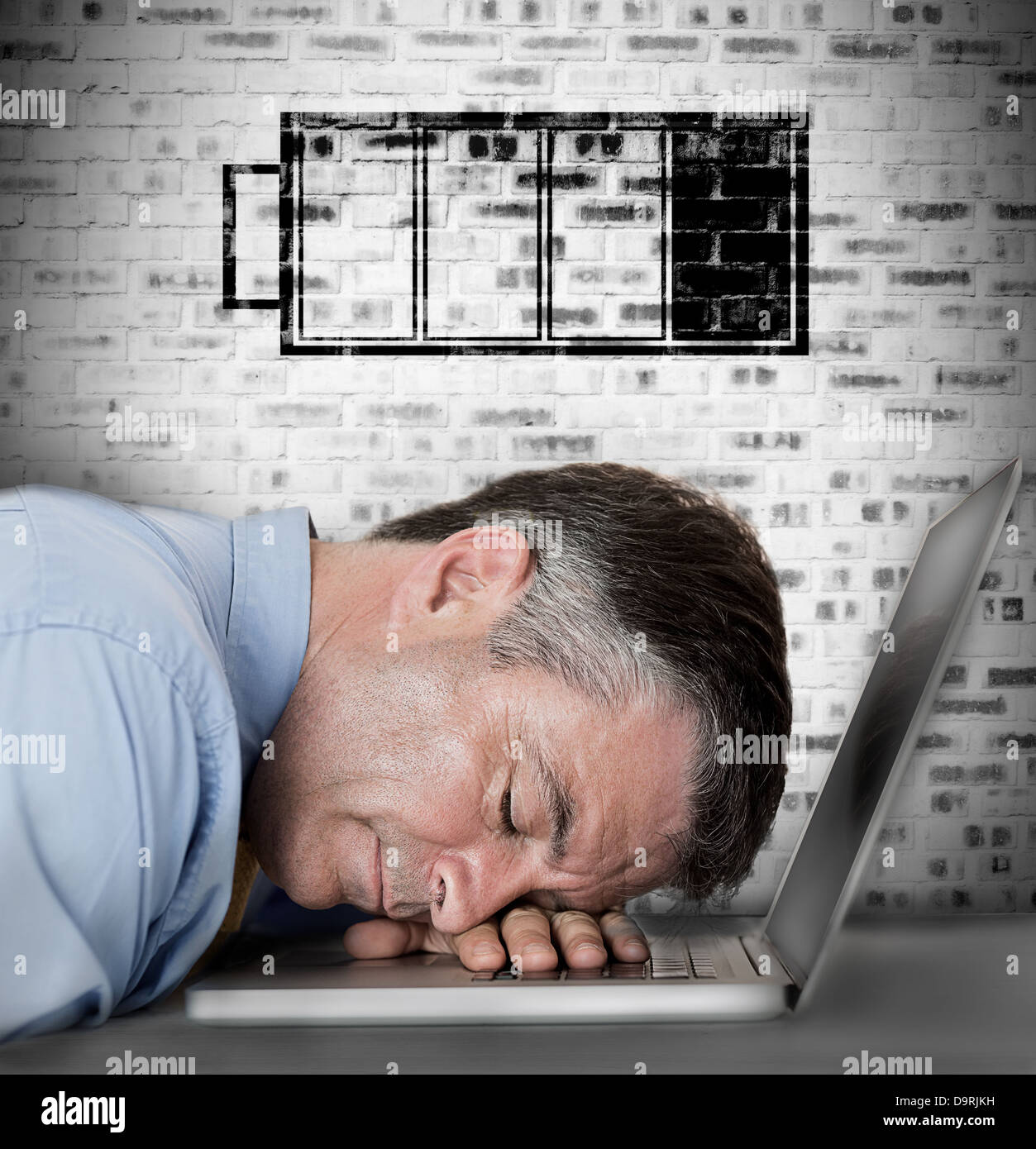 Businessman sleeping on his laptop with low battery symbol - Stock Image