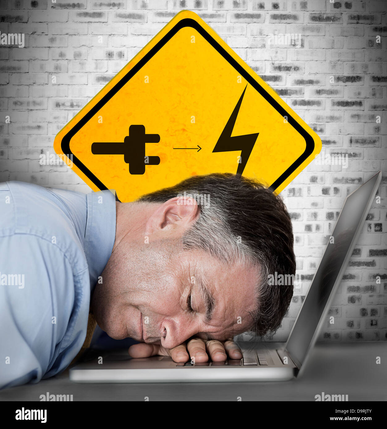 Businessman sleeping on his laptop with battery plug roadsign - Stock Image