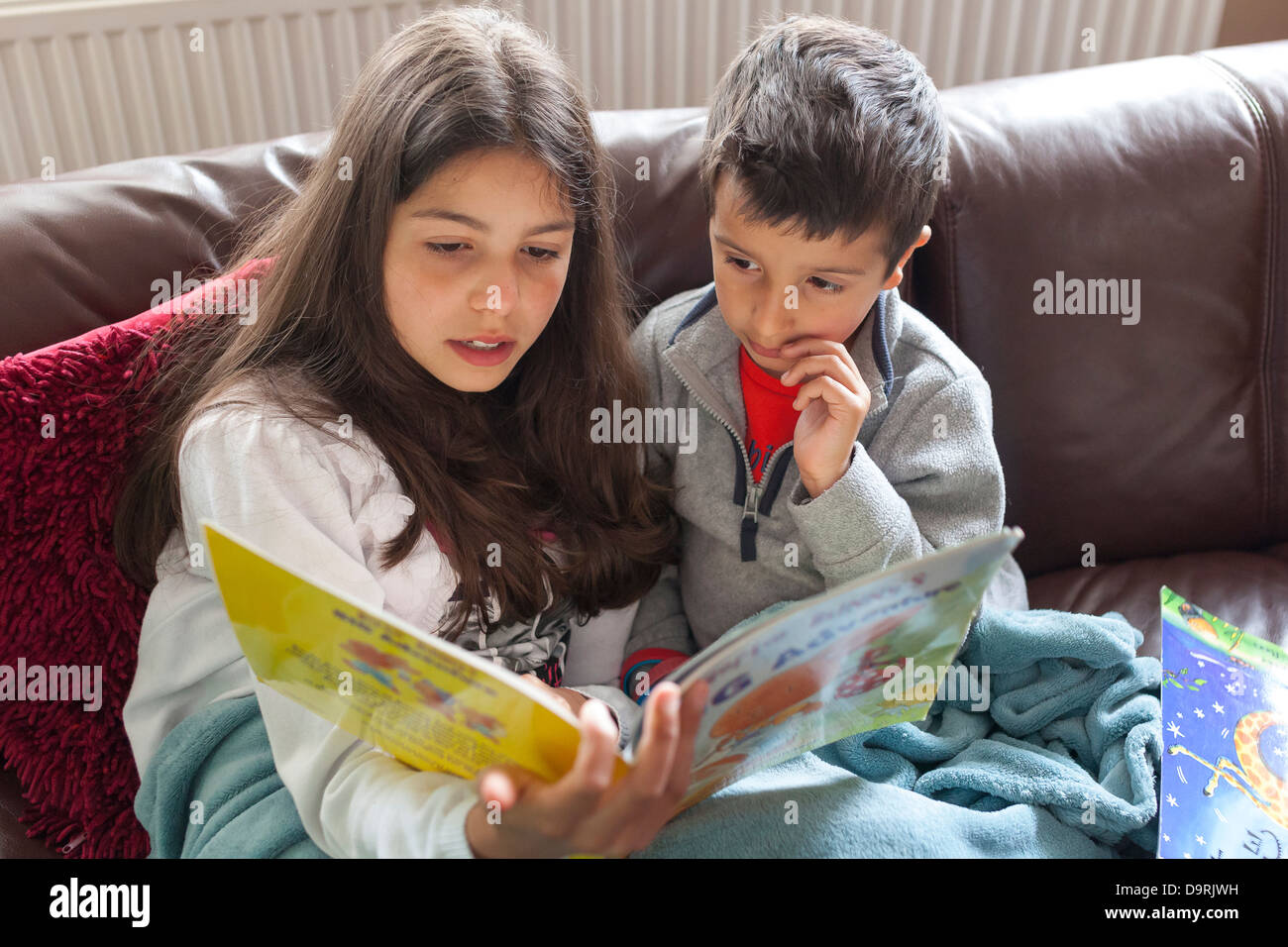 Older sister reading a story to her brother - Stock Image