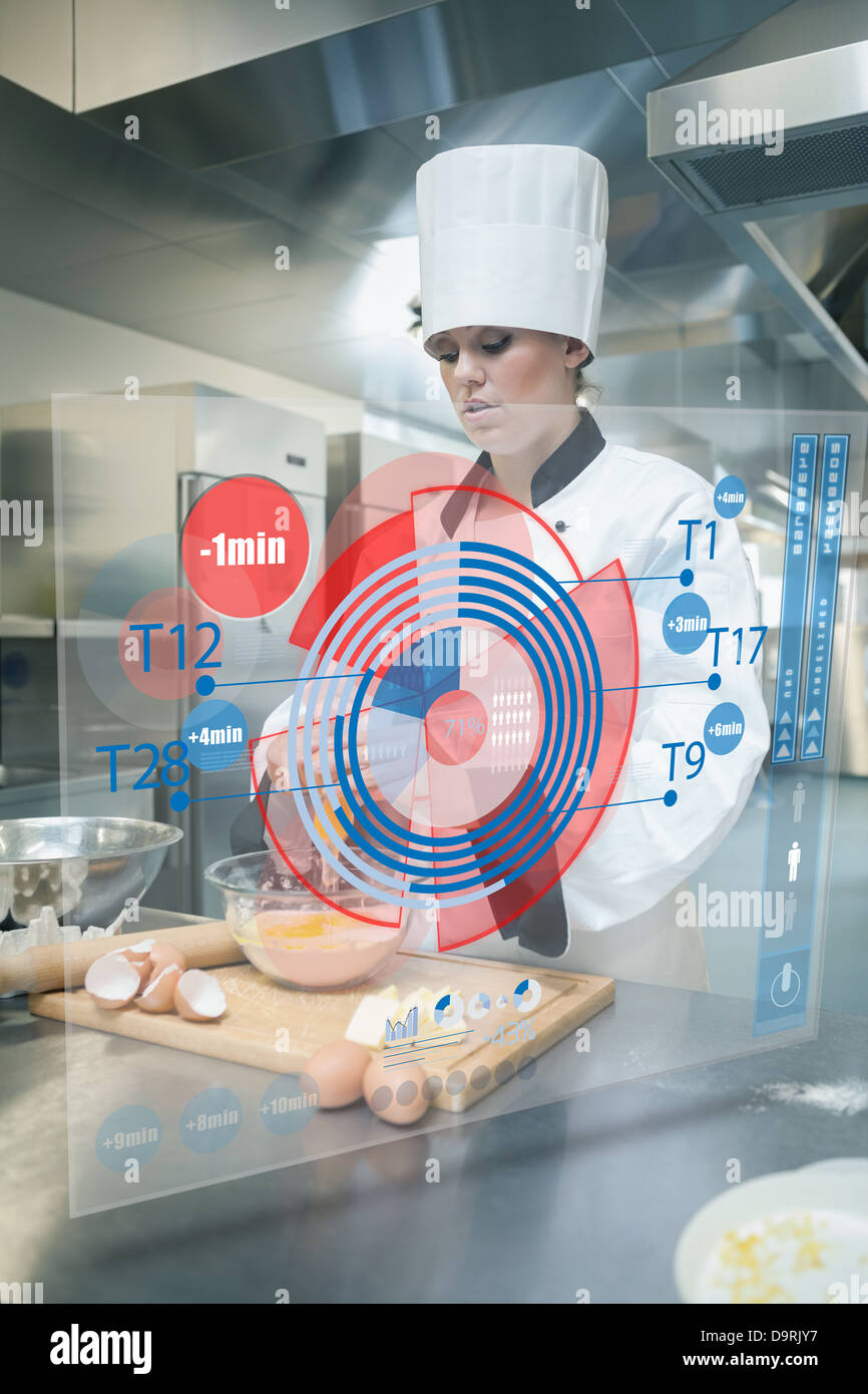 Pastry chef making dough while consulting futuristic interface - Stock Image