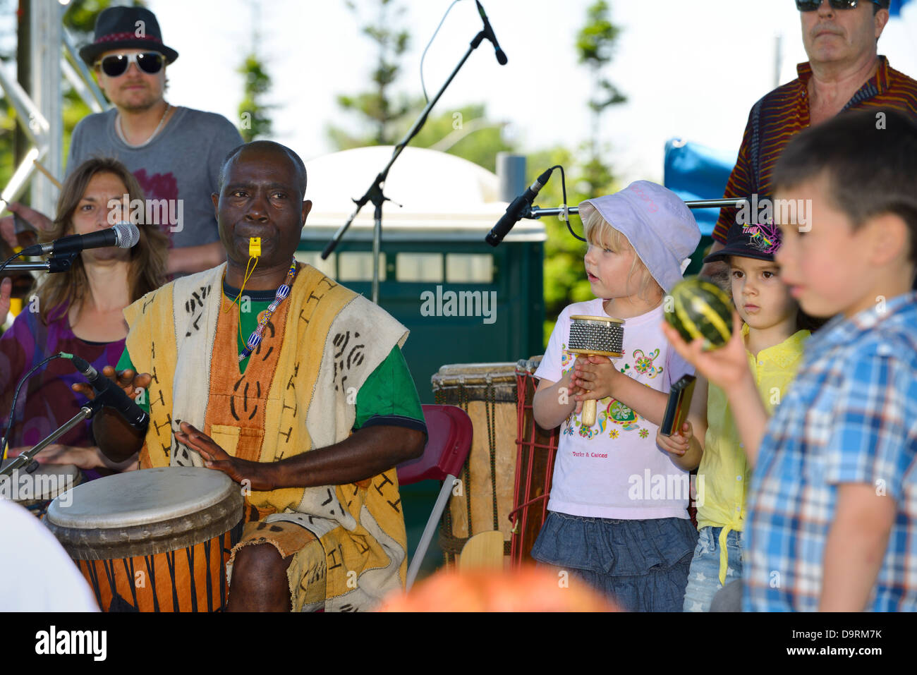 Njacko Backo African djembe drummer performing on stage with children at the Muhtadi Drum Festival Toronto - Stock Image