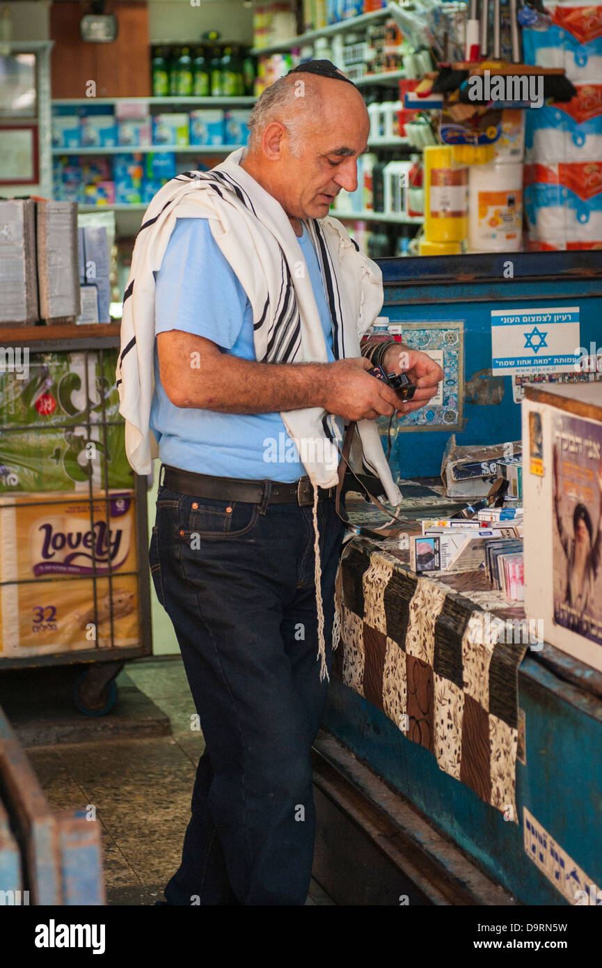 Israel Tel Aviv Carmel Market middle aged man male ties Tefillin Phylacteries praying containing parchment scroll - Stock Image