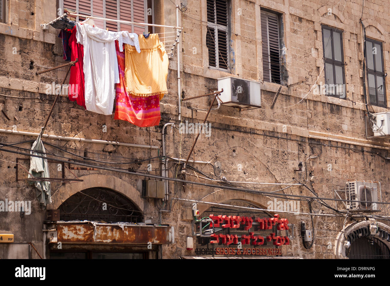 Israel Jaffa Yafo Old City street scene washing laundry hanging on line outside window over shops stores road colourful - Stock Image