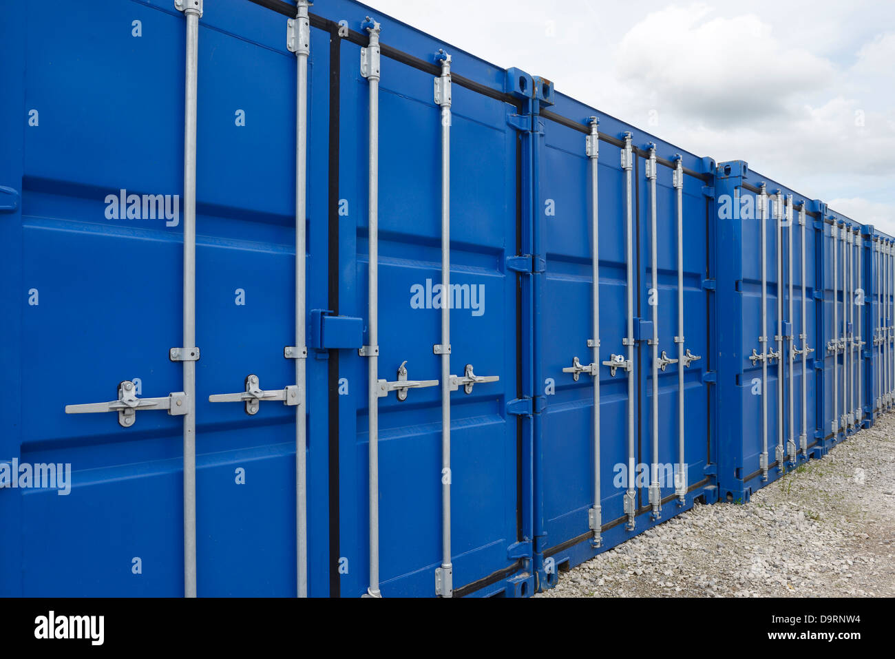 Row of blue metal shipping containers - Stock Image