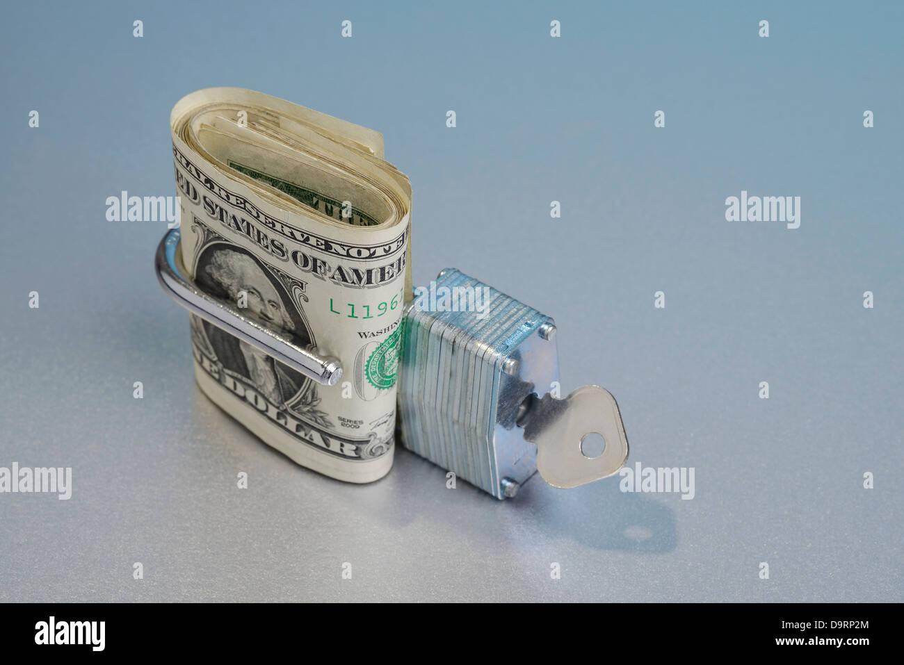 Dollar bills in an open padlock - Stock Image