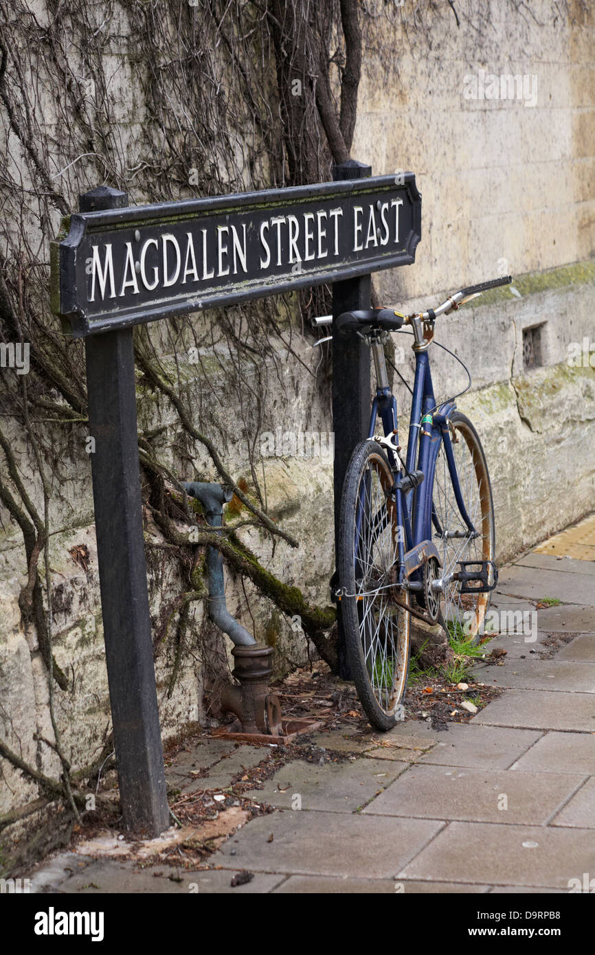 Bike leant against sign for Magdalen Street East at Oxford in May - Stock Image