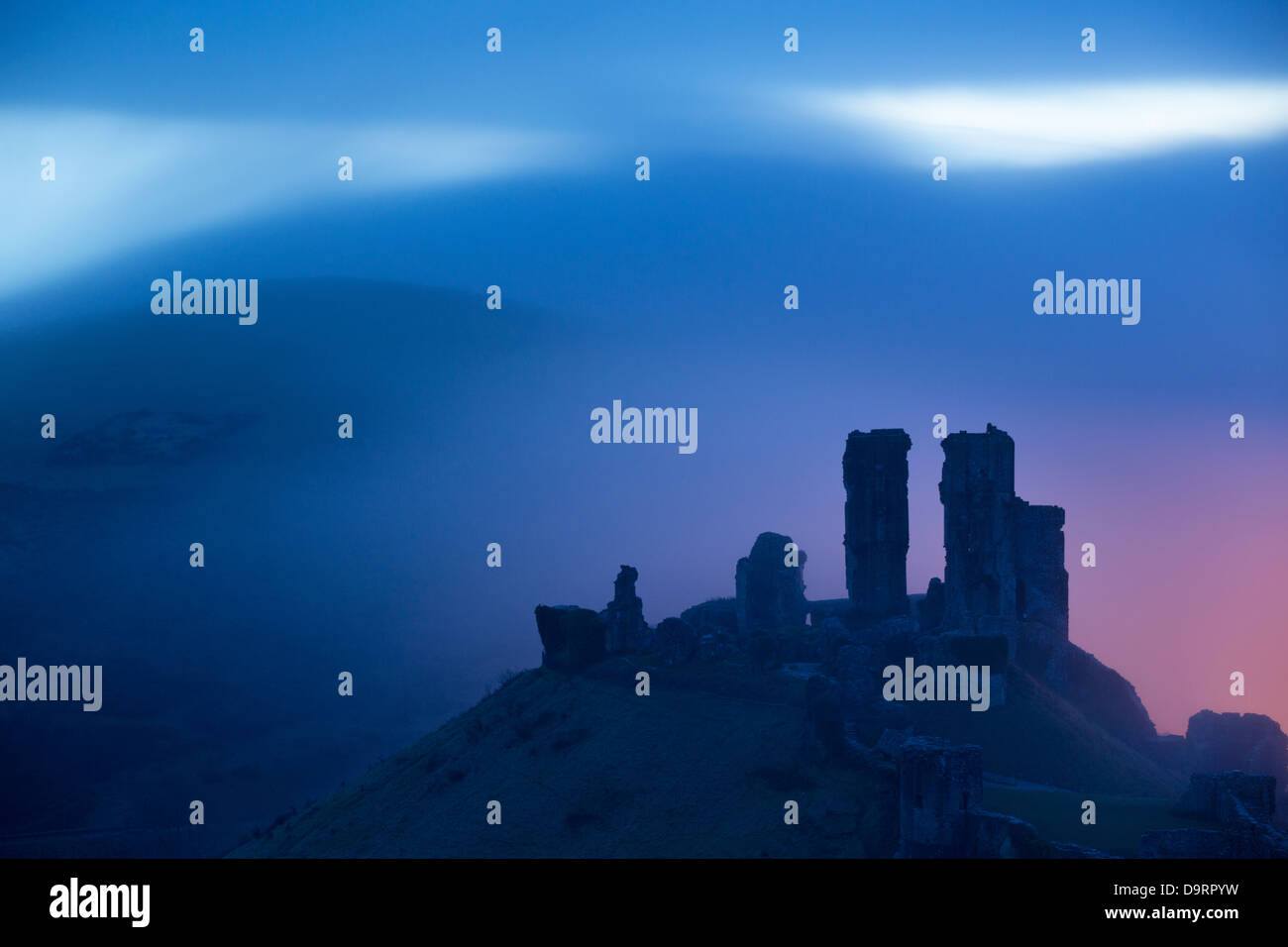 Corfe Castle in the mist at dawn, Dorset, England, UK - Stock Image