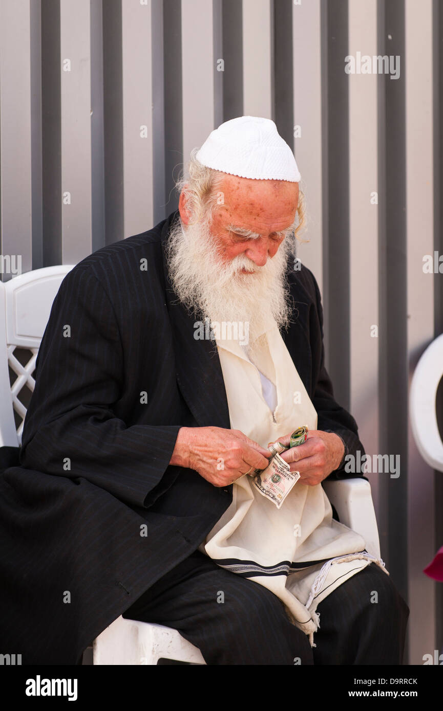 Israel Jerusalem Old City white bearded Orthodox Jew sitting counting money helper at Wailing Western Wall Ha Kotel - Stock Image