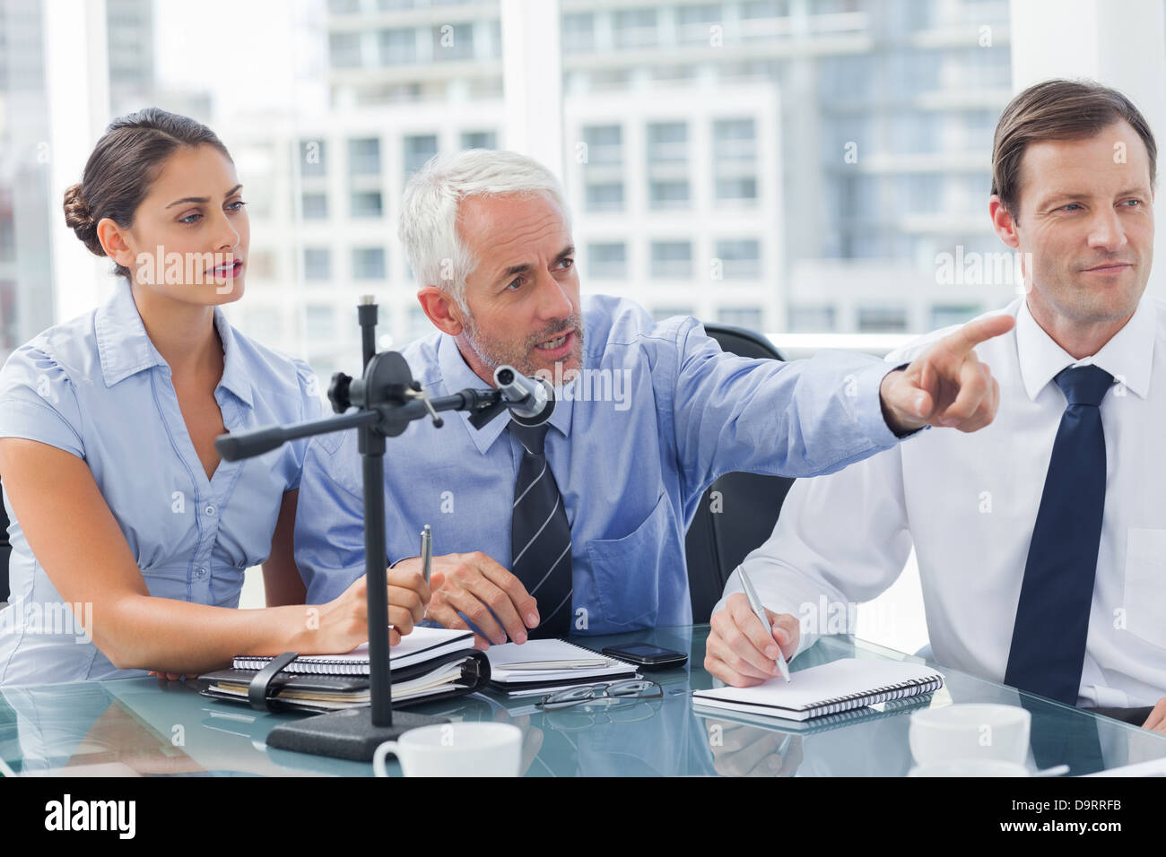 Business man pointing at something in a conference - Stock Image
