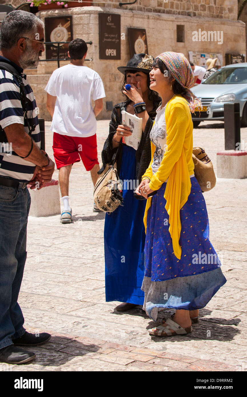 Israel Jerusalem Old City Hurva Square 2 two pretty young Japanese tourist tourists girls shawls hats long skirts - Stock Image