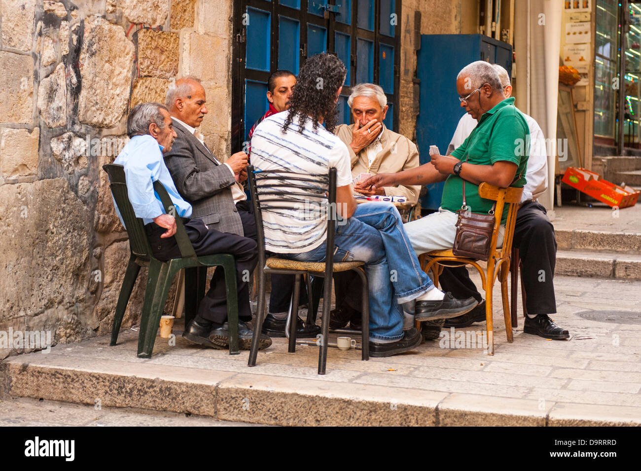 Israel Old City Jerusalem street scene intense group of Arab Muslim men playing cards card game seated around table - Stock Image