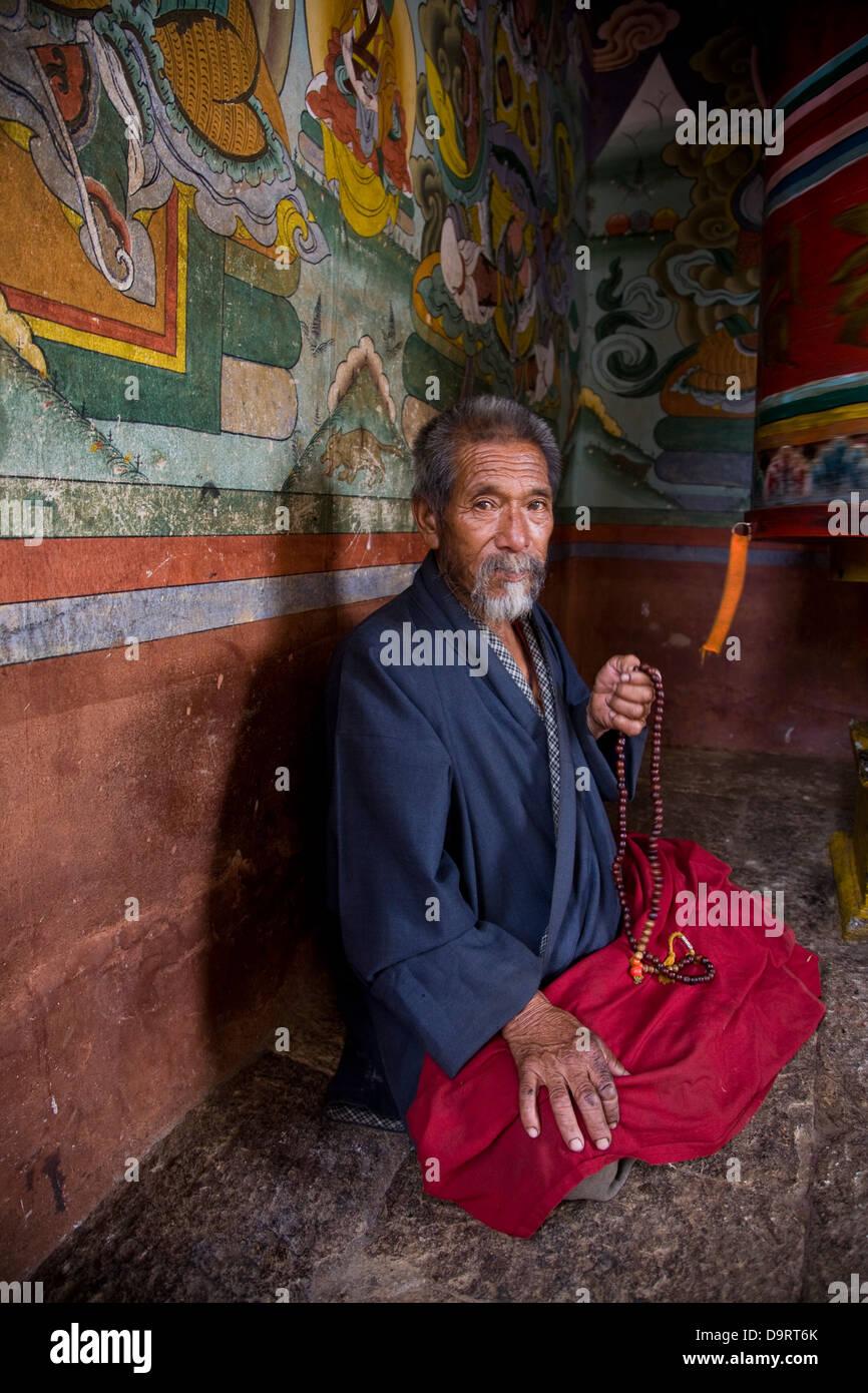 A Bhutanese Man in prayer at the prayer wheel at Chimi Lakang,  Punakha Valley, Bhutan, Asia - Stock Image