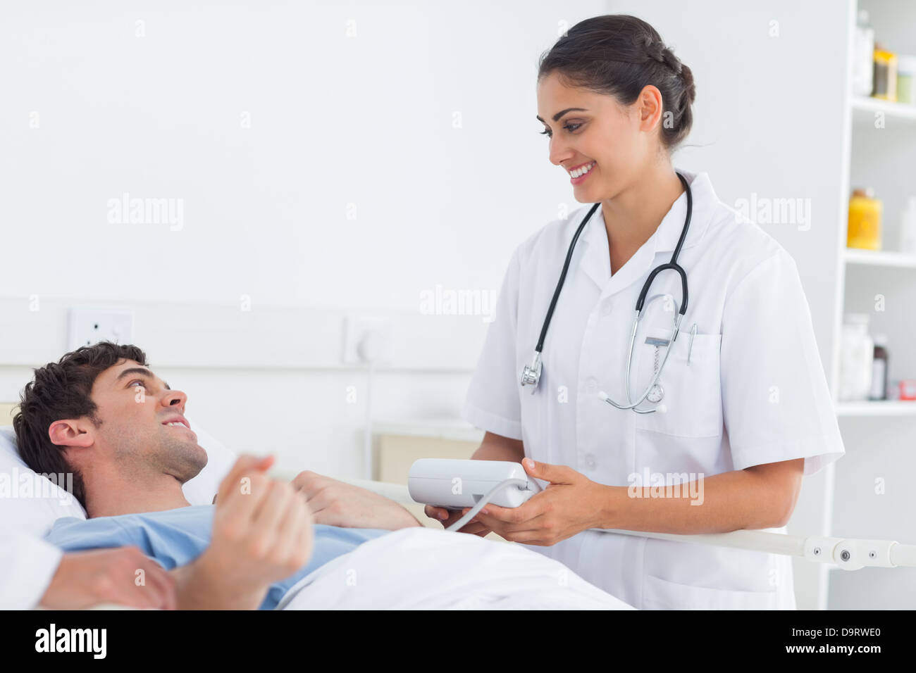 Attractive doctor taking the blood pressure of a patient - Stock Image