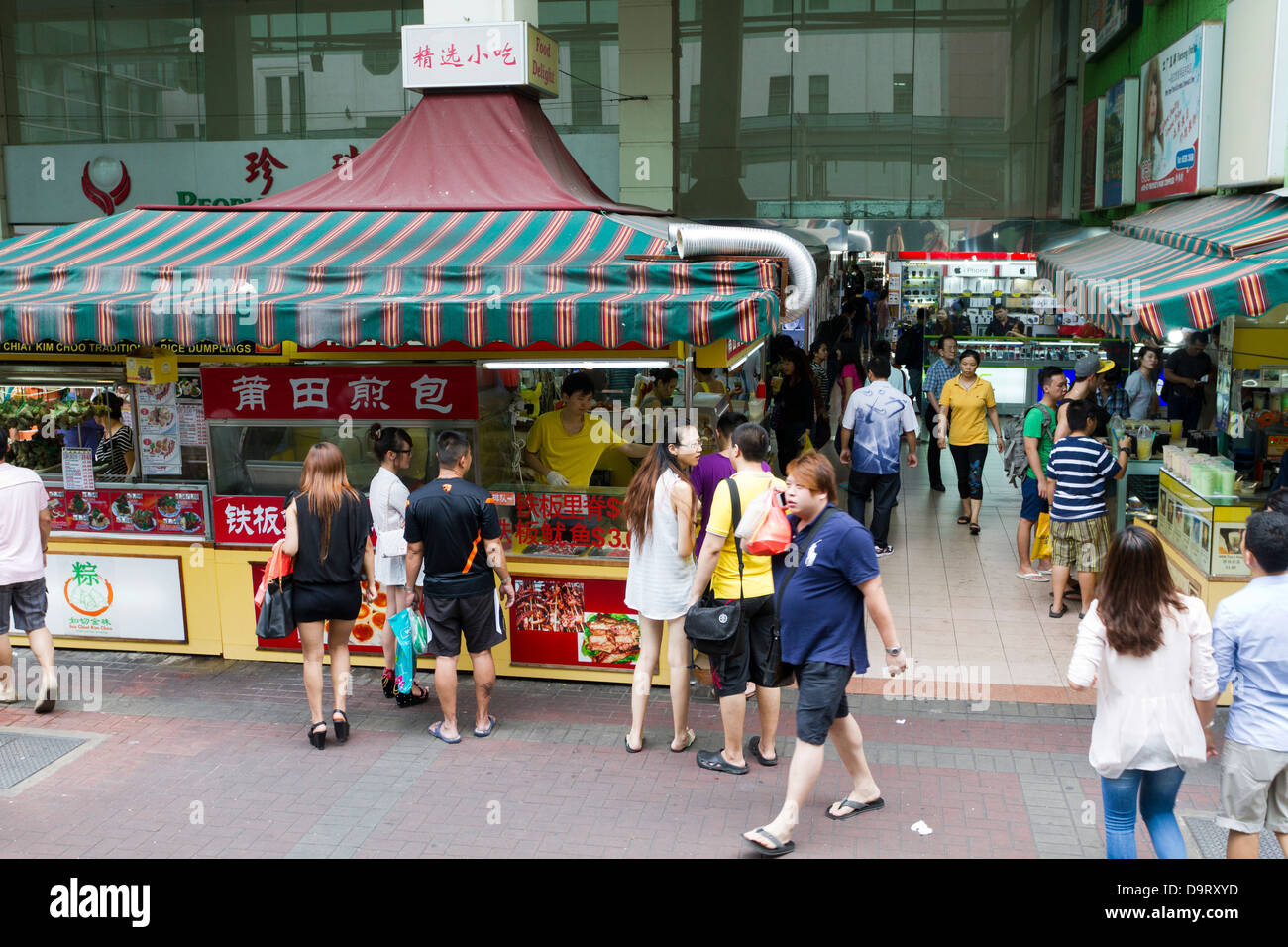 People buying food at stalls in Chinatown, Singapore - Stock Image