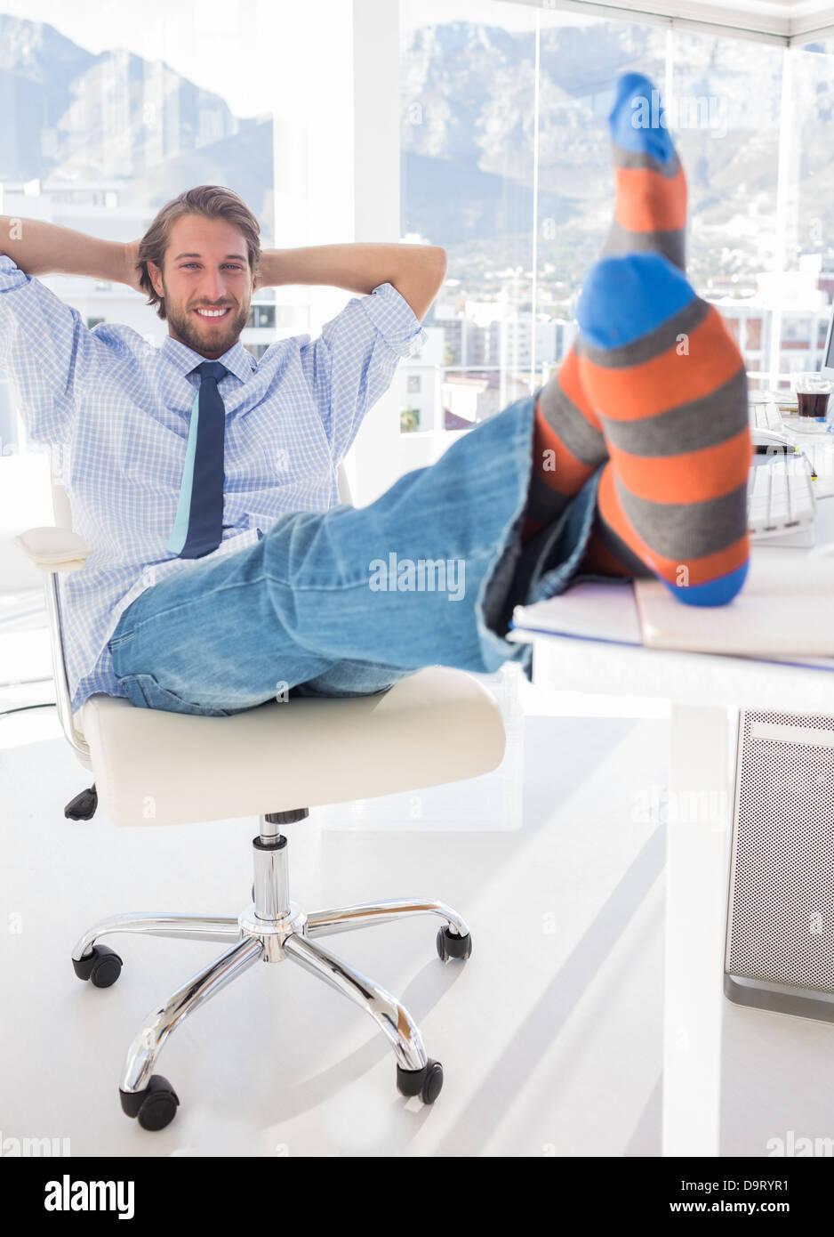 Shoeless designer kicking back - Stock Image