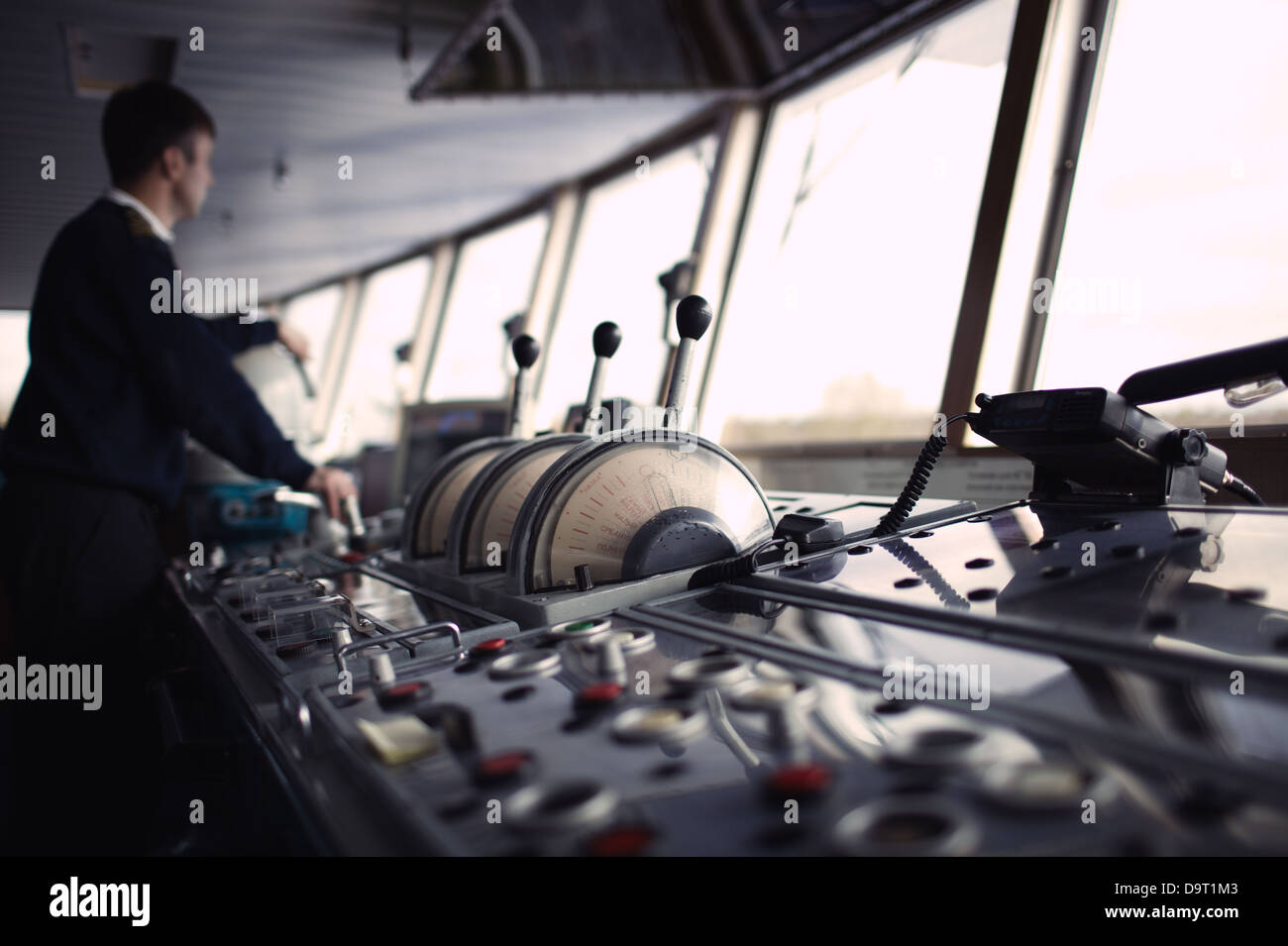 Navigation officer driving ship on the river. - Stock Image